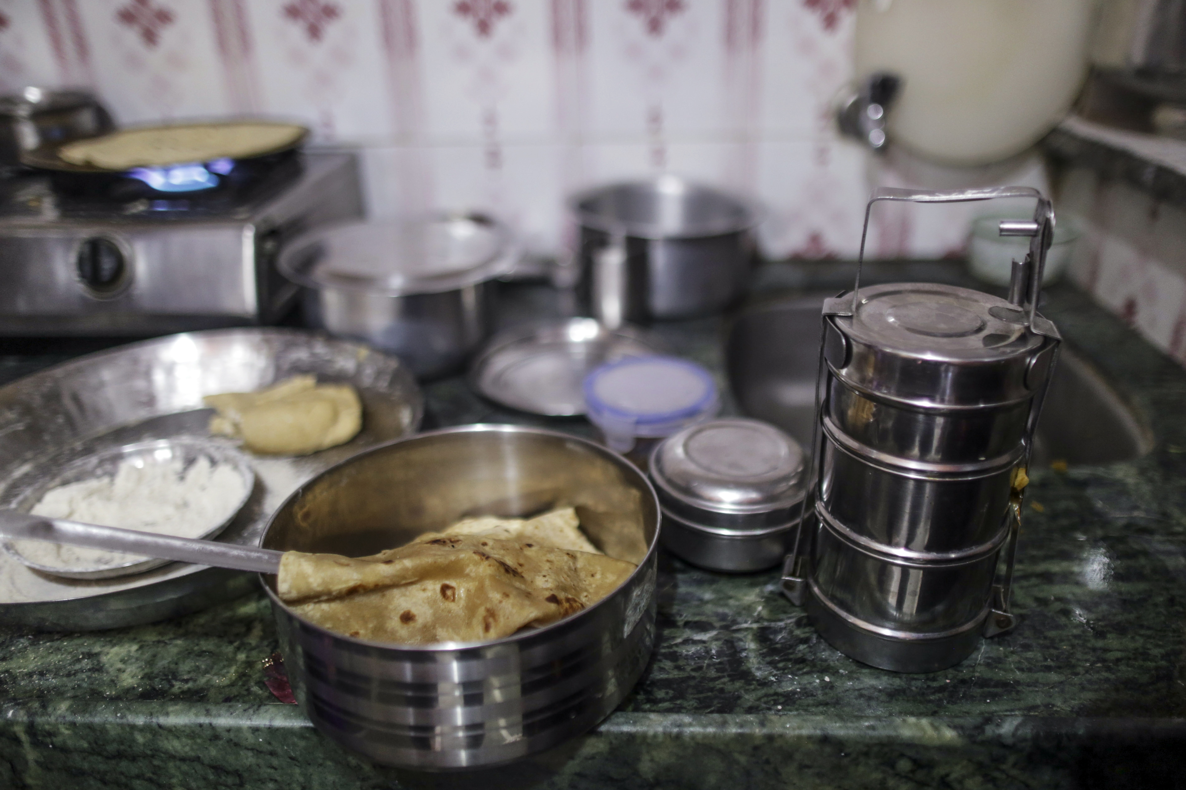 Indian bread sits inside a tiffin boxon a kitchen counter