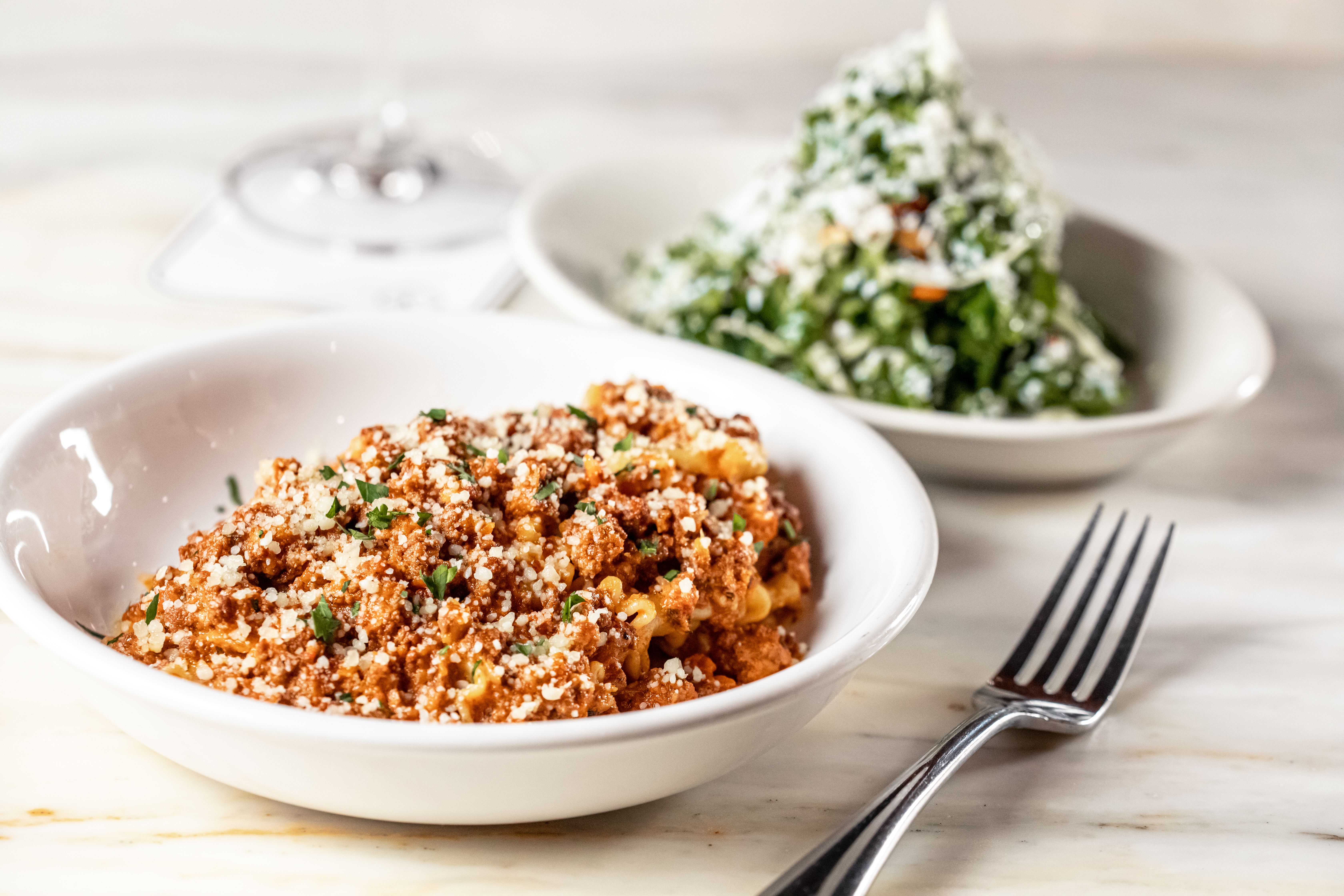 Pasta bolognese served in a white bowl