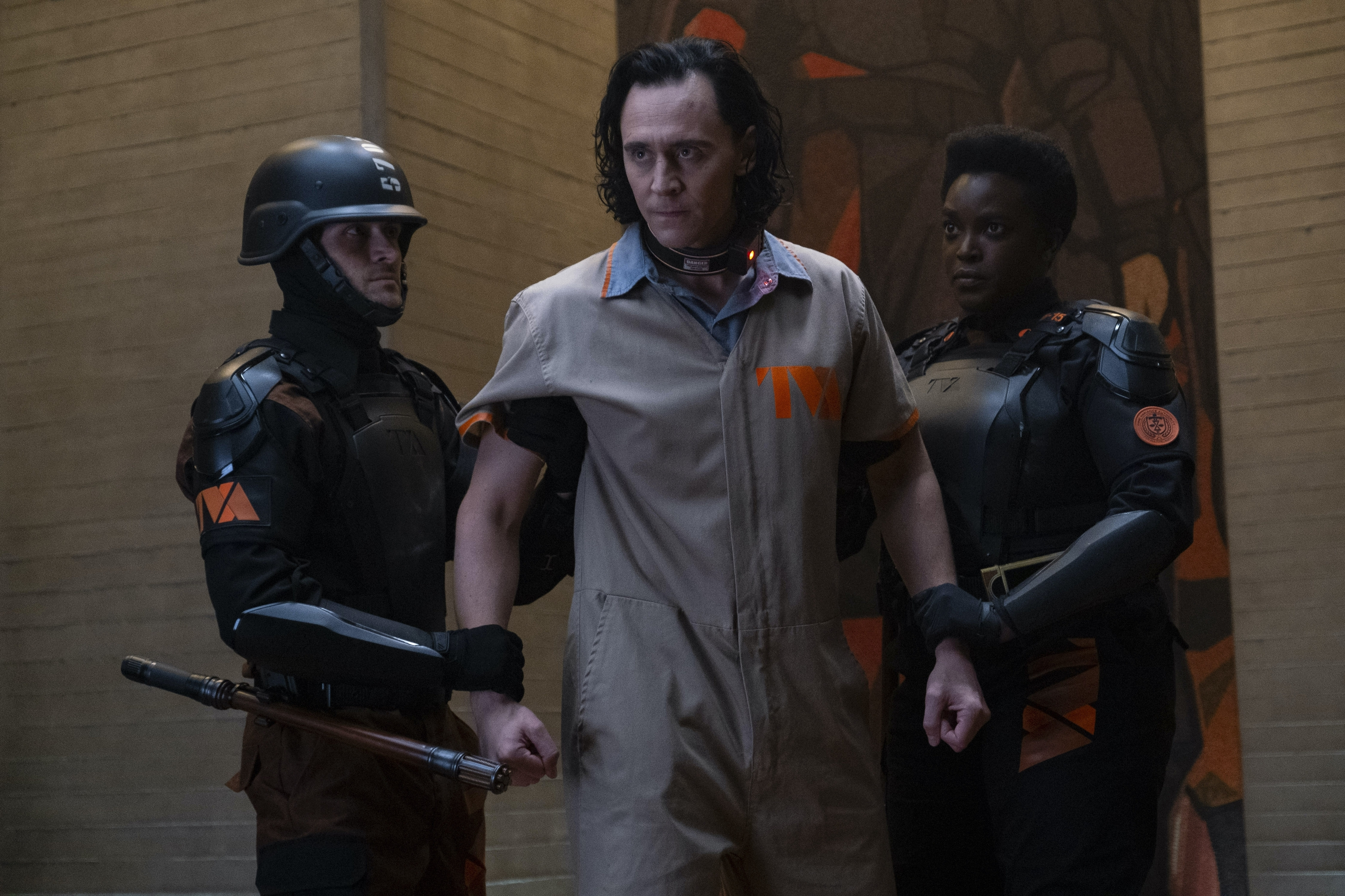 Tom Hidddleston as Loki being restrained by a guard on either side.