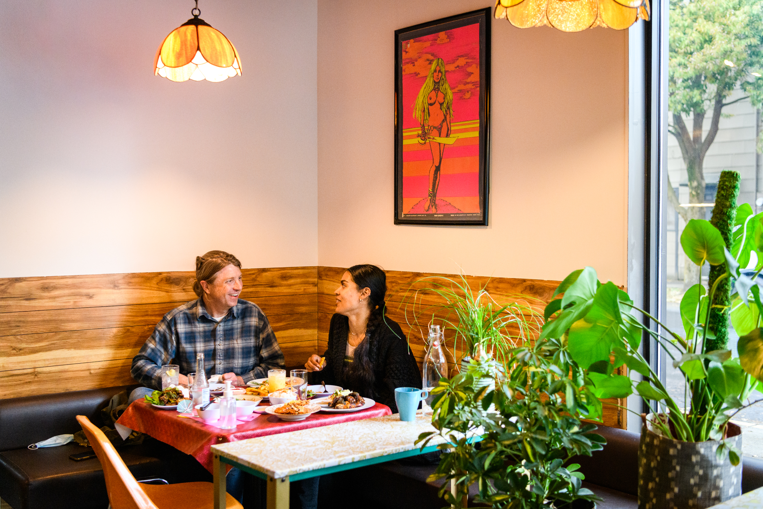 A man in a plaid shirt and a woman in a black shirt sit at a corner table at Oma's Hideaway eating food on pink trays.