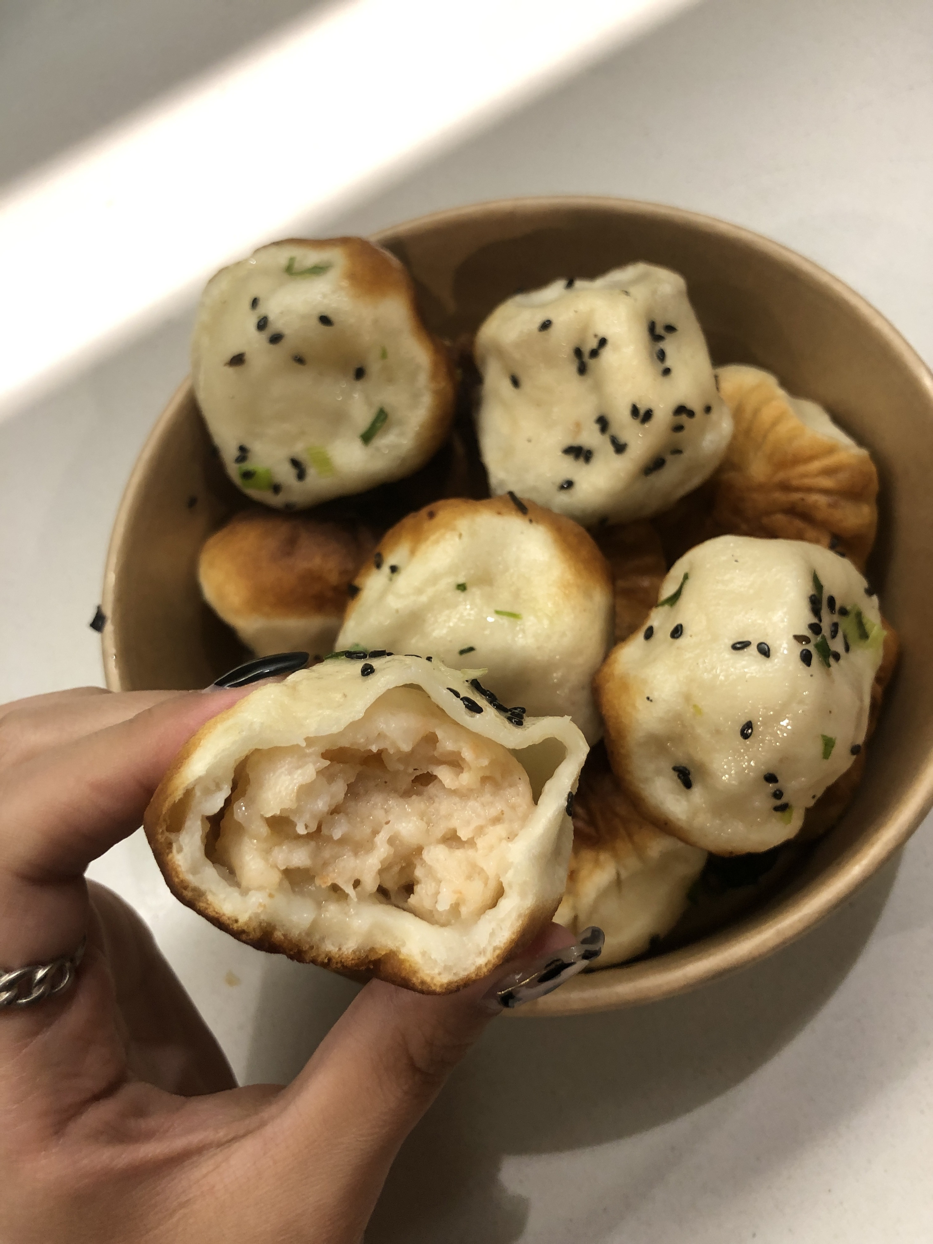 hand holding shrimp dumpling half bitten into
