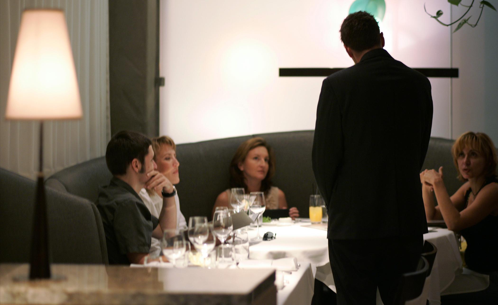 在La J的Jack 's餐厅的高级餐厅里,一名服务员正在和顾客谈论菜单