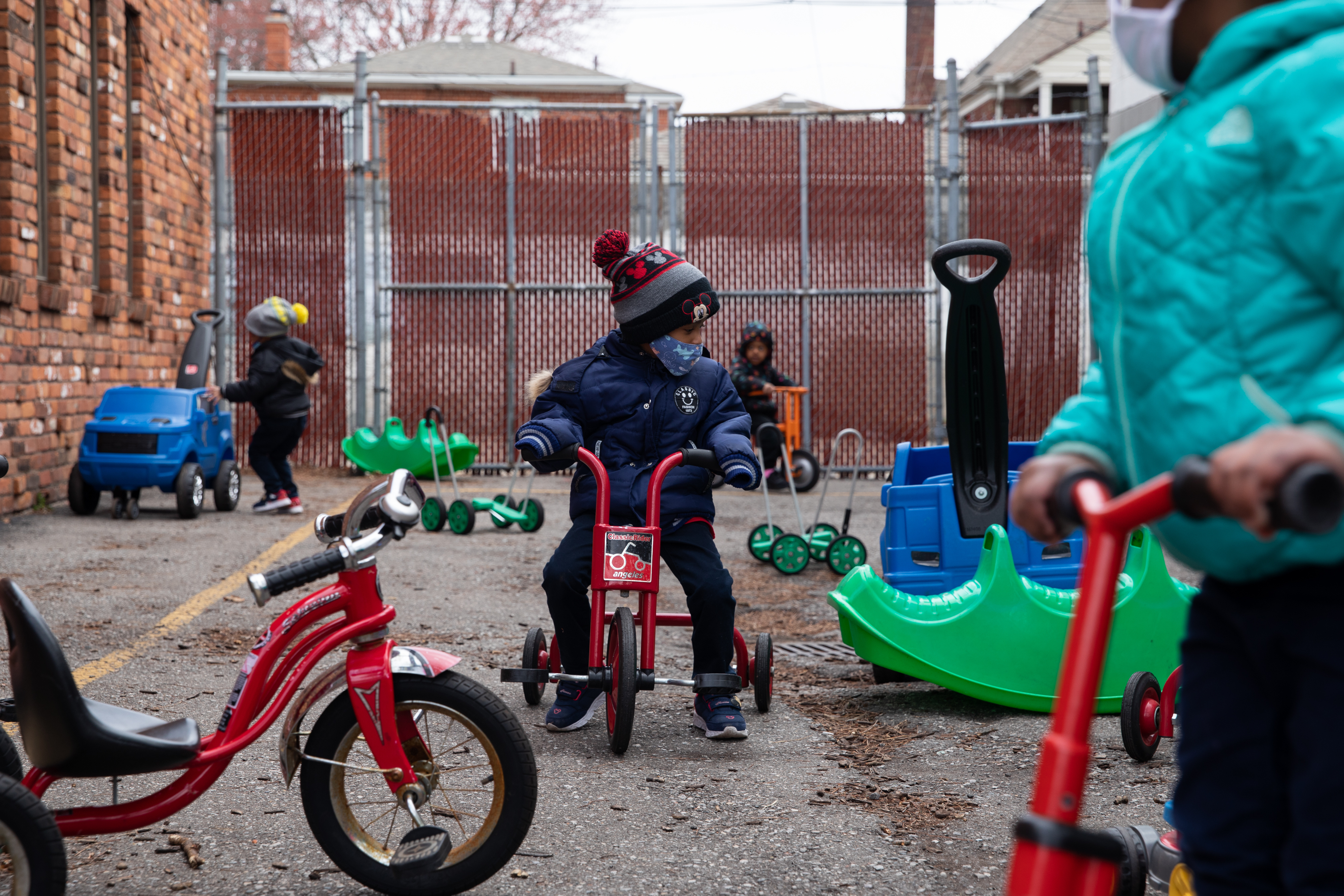 Preschoolers ride around on scooters outside at Little Scholars child care center in Detroit, Michigan, U.S., on Thursday April 1, 2021.