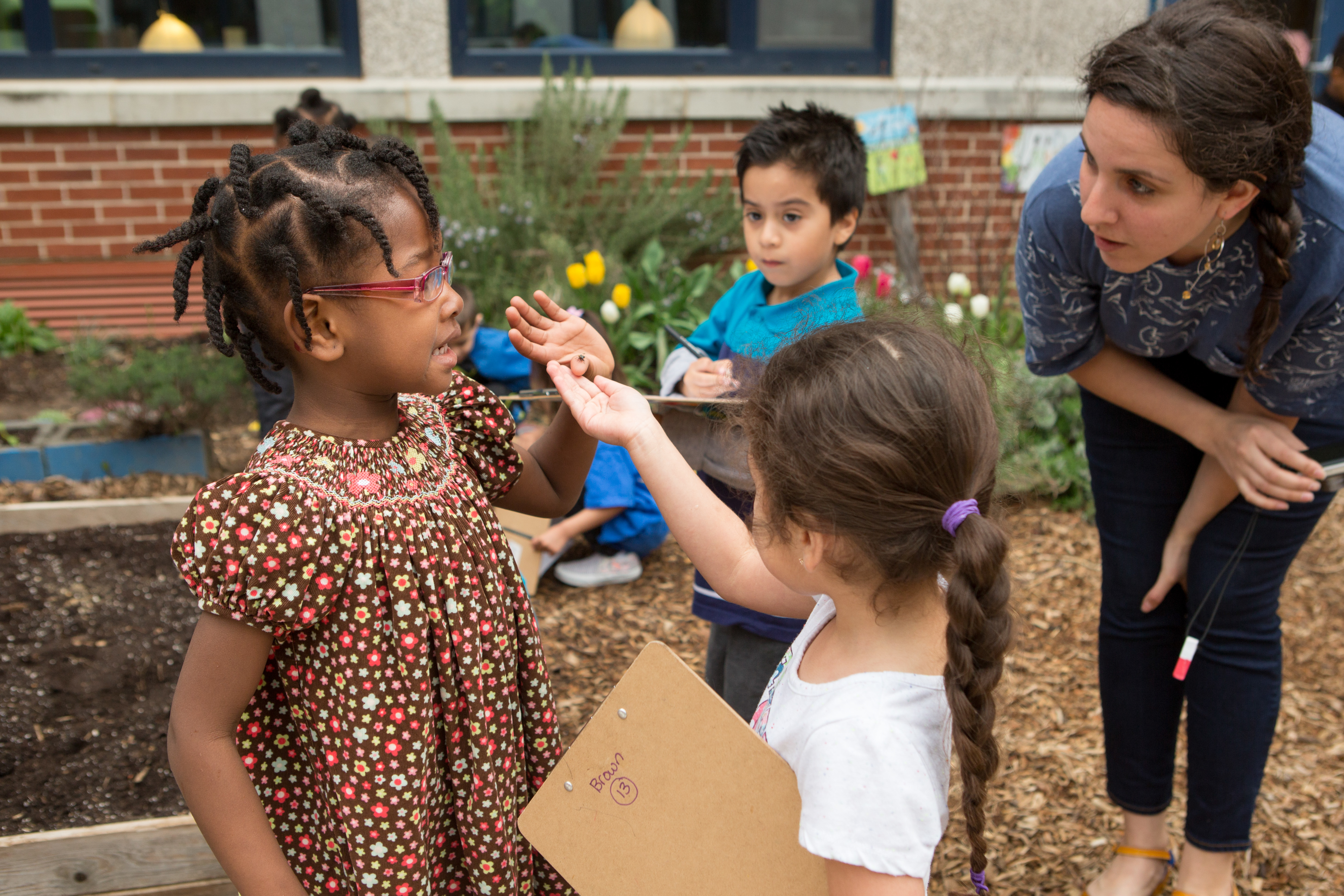A preschool girl stands outside holding an insect on her finger while a classmate and a teacher look at it.