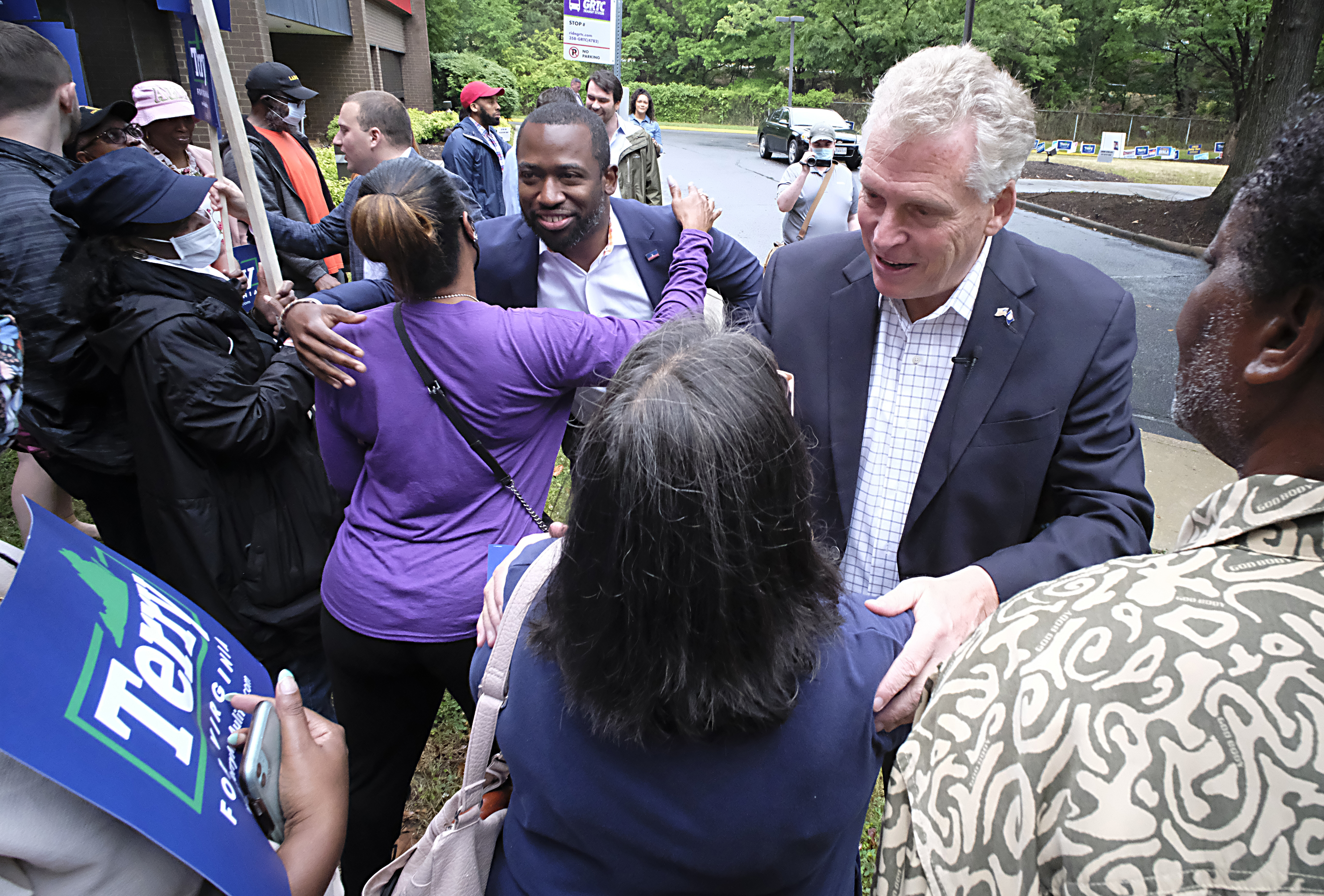 Former Virginia governor Terry McAuliffe, right, and Richmond Mayor Levar Stoney, left, greet McAuliffe supporters during a quick rally outside the Office of the General Registrar, City of Richmond, in Richmond, Va. Friday, June 4, 2021. McAuliffe is running for the gubernatorial nomination in the upcoming Democratic Primary.