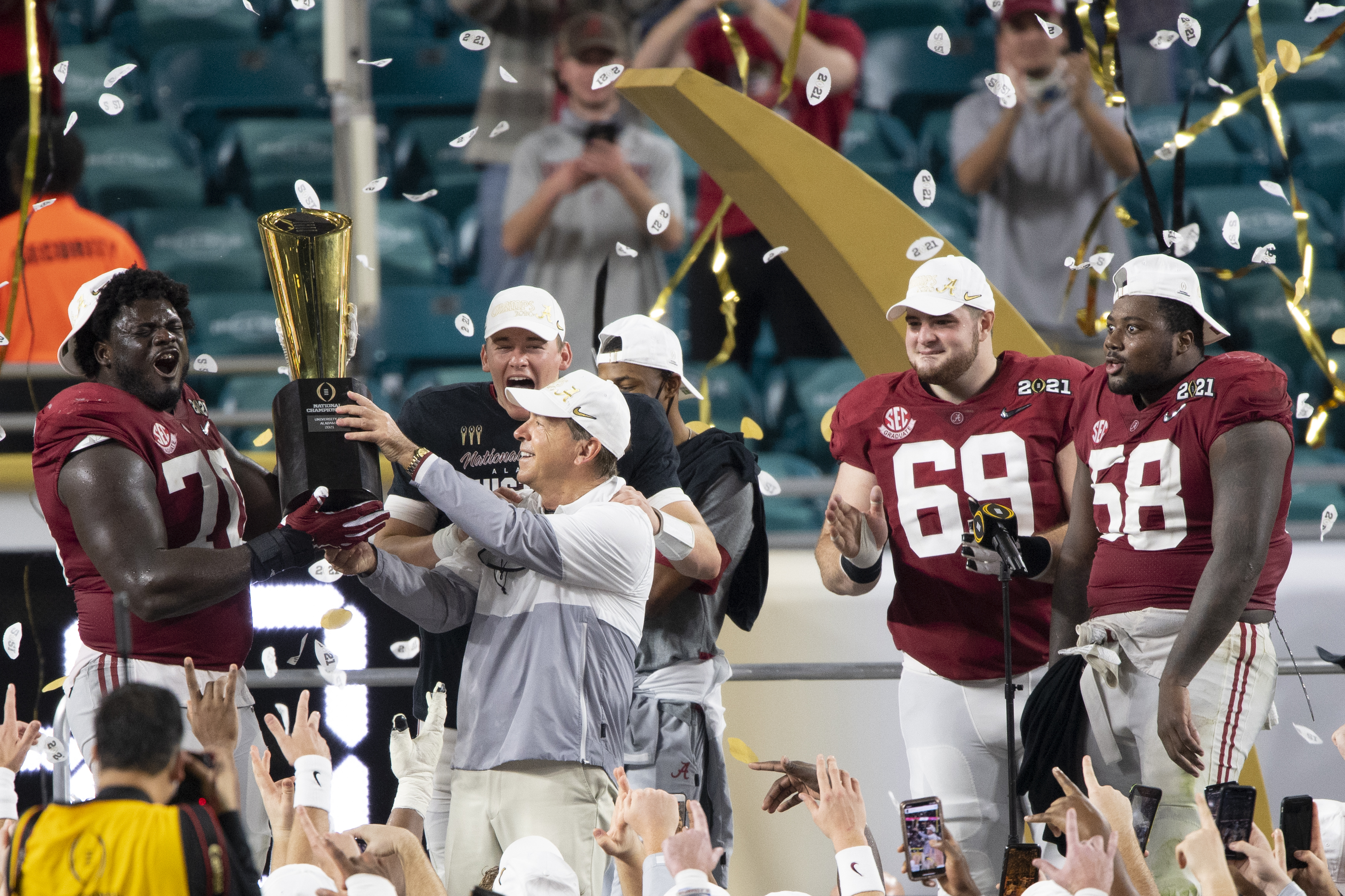 Alabama Crimson Tide offensive lineman Alex Leatherwood and Alabama Crimson Tide head coach Nick Saban hold the trophy as they celebrate on the stage.