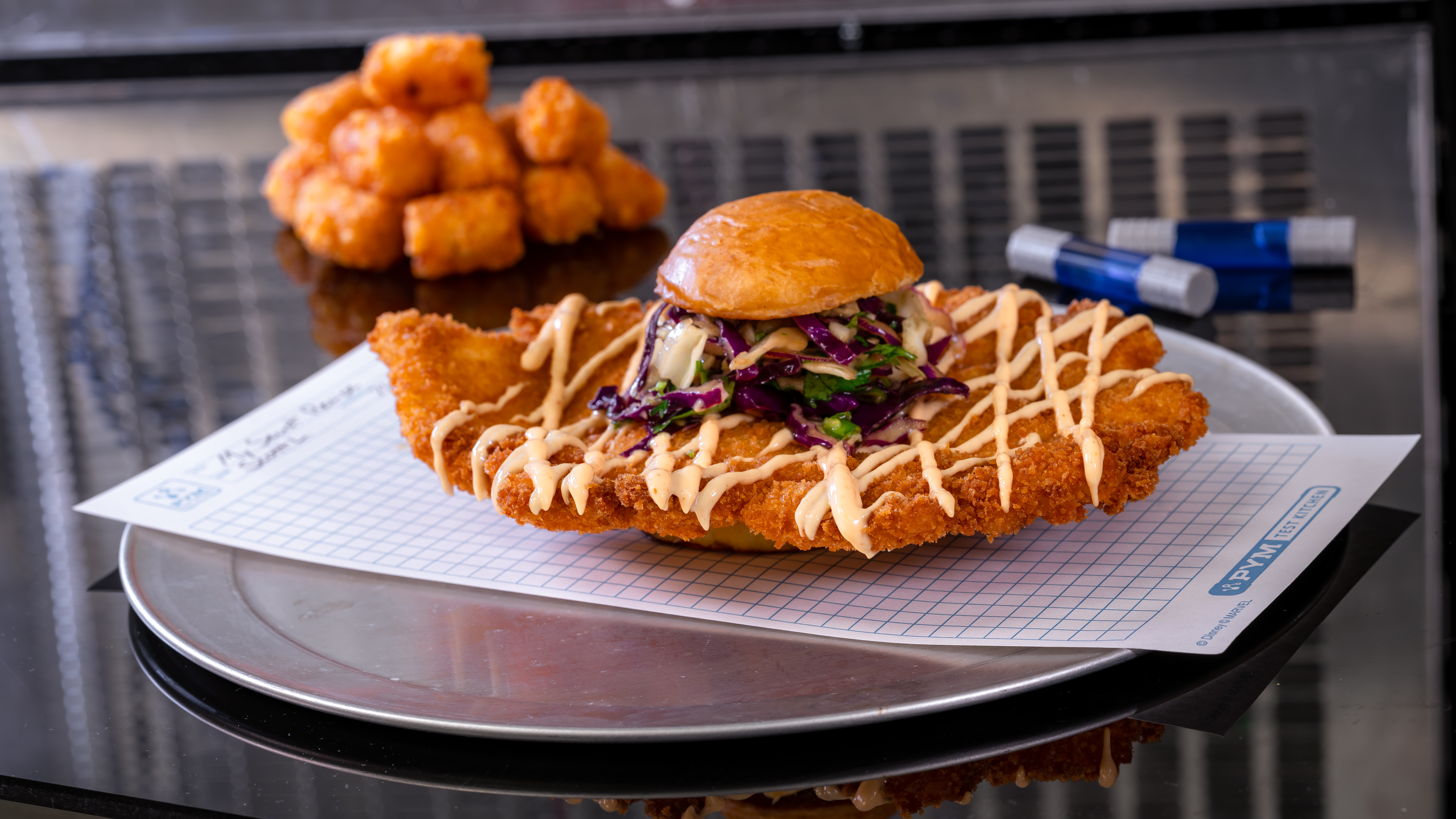A giant fried chicken patty hangs out of the sides of a small bun sandwich with tater tots on the side
