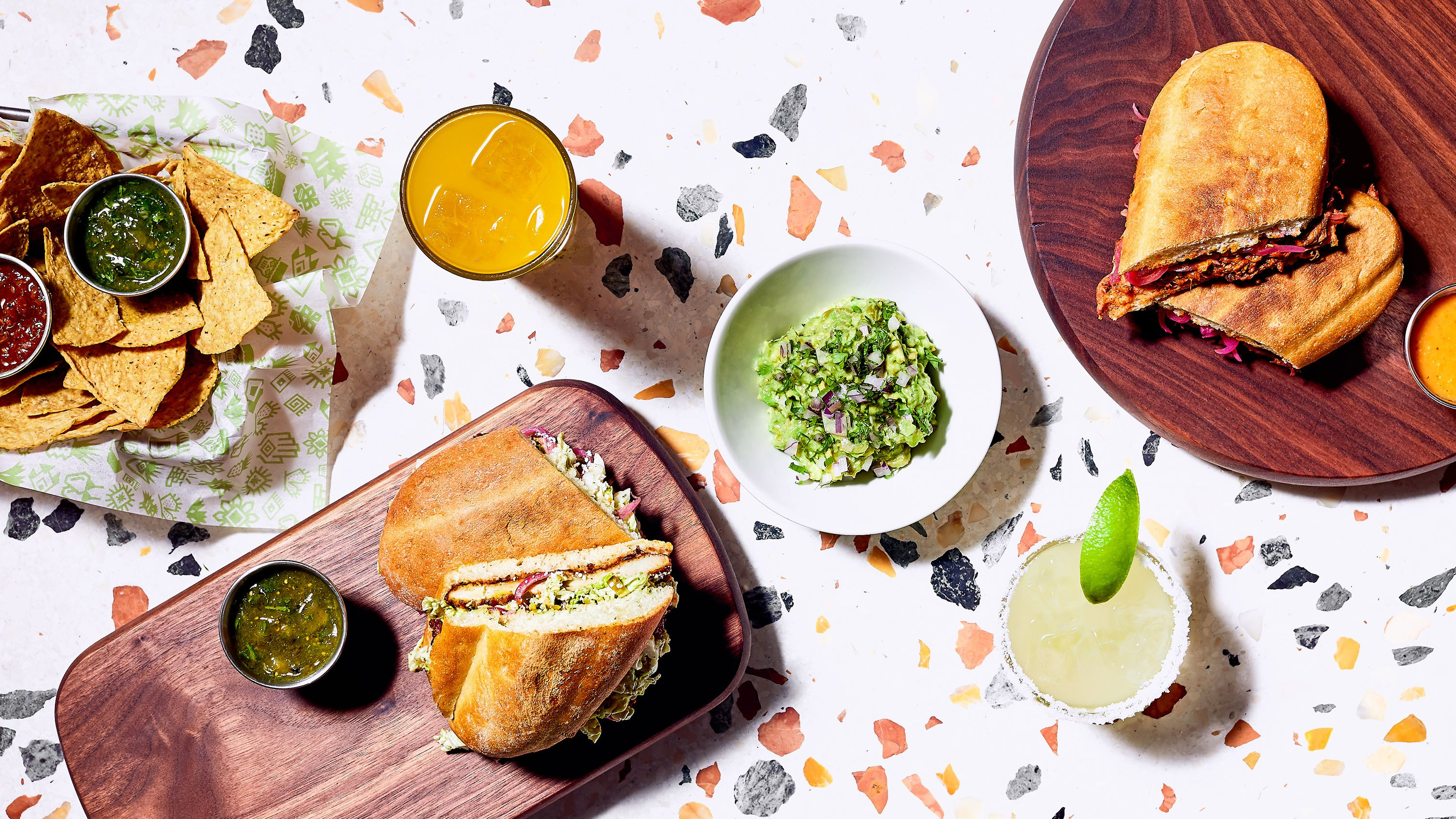 A collection of Mexican plates and drinks on a white background.