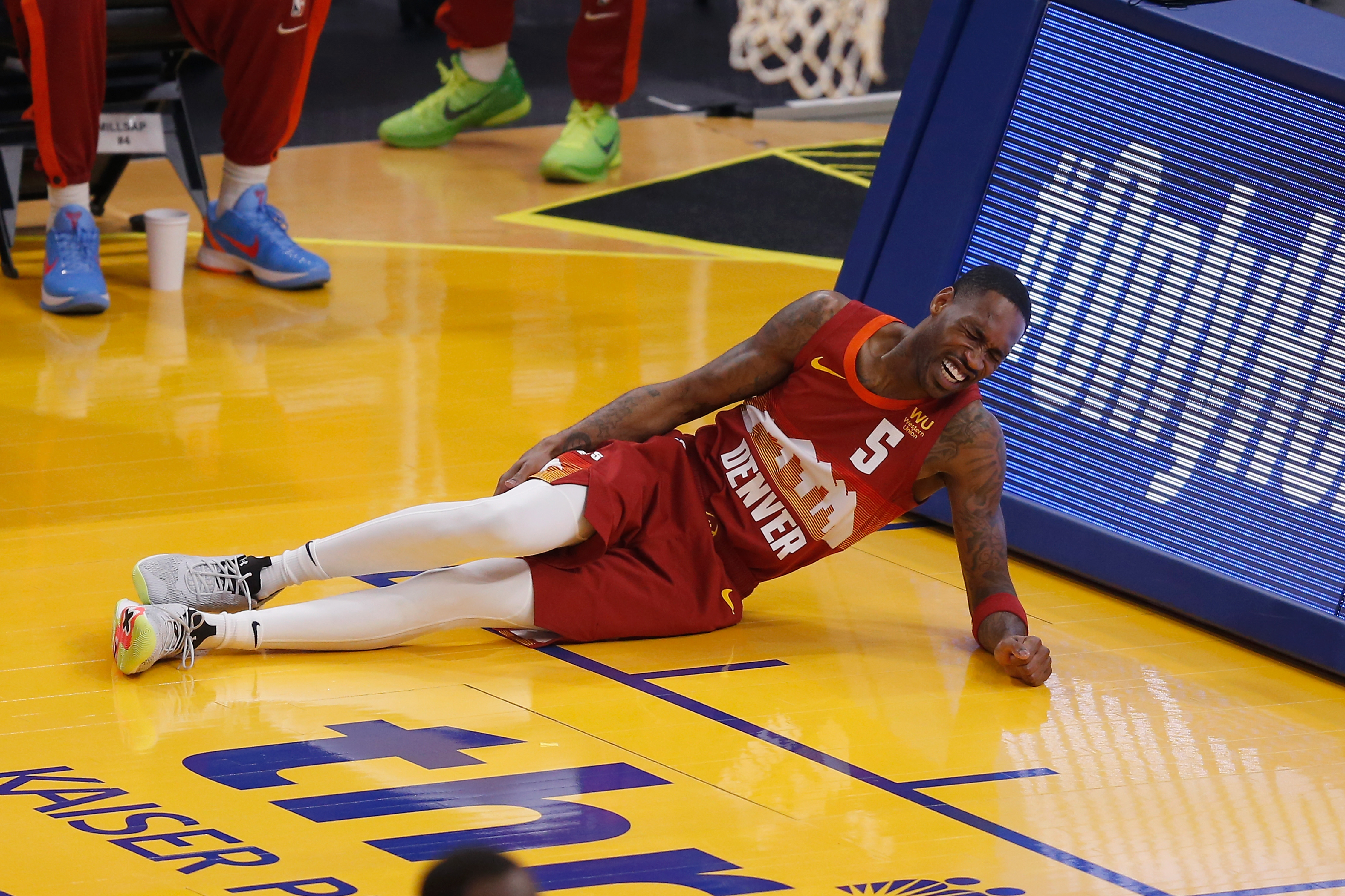 Will Barton of the Denver Nuggets grasps his leg after a play in the first quarter against the Golden State Warriors at Chase Center on April 23, 2021 in San Francisco, California.