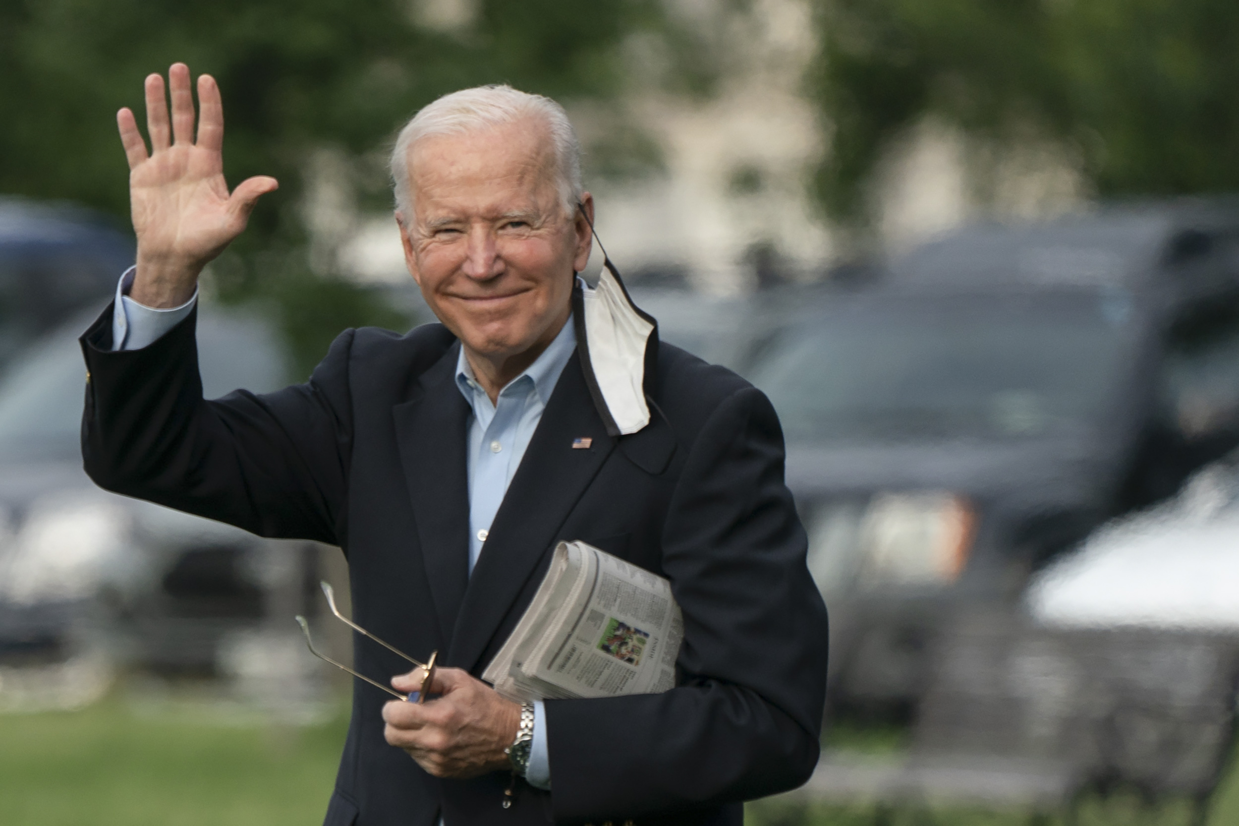 President Biden waves as he crosses the White House lawn.