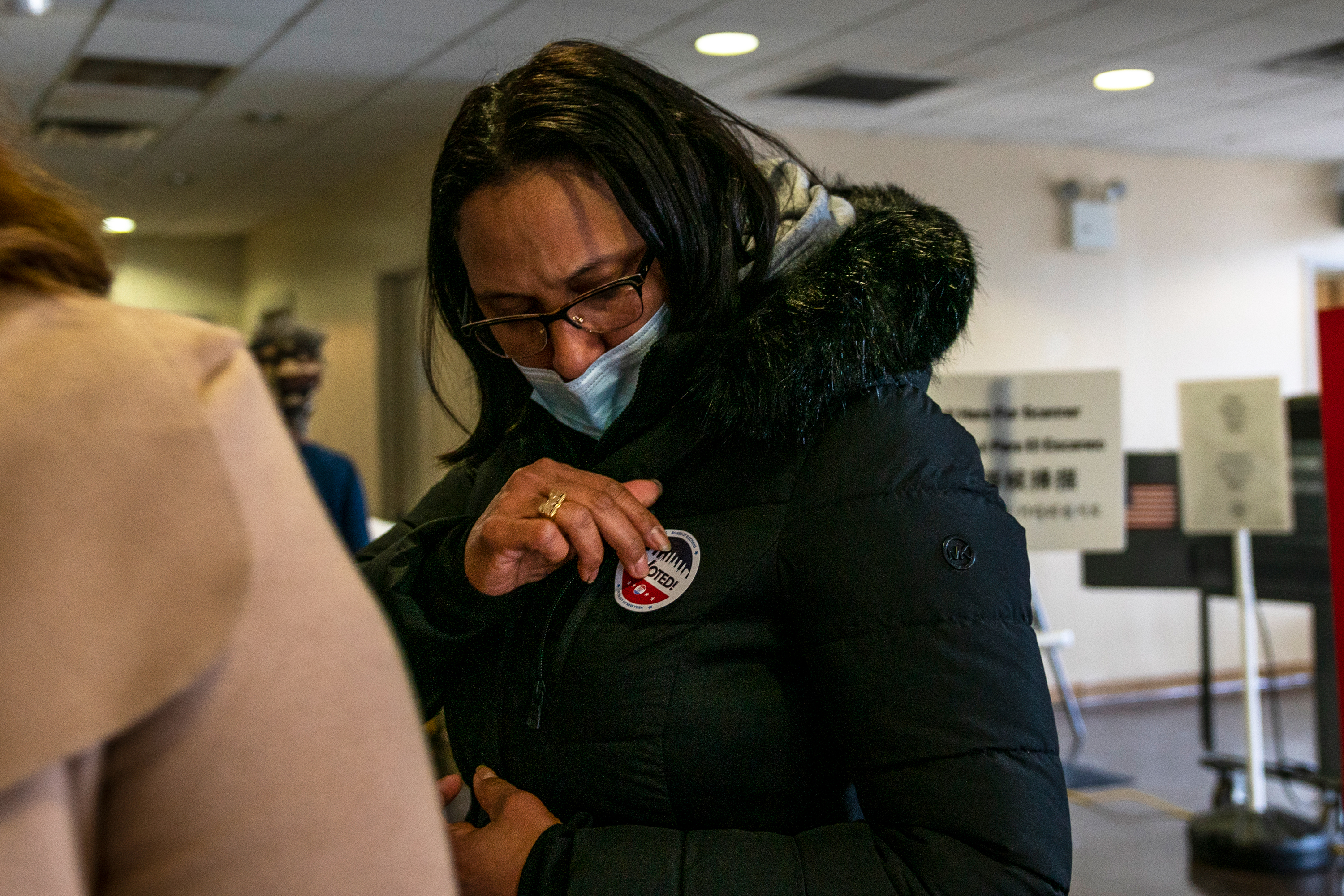 Milva Ventura, 46, puts on an election sticker at her Bronx polling place after voting for the first time, Nov. 3, 2020.