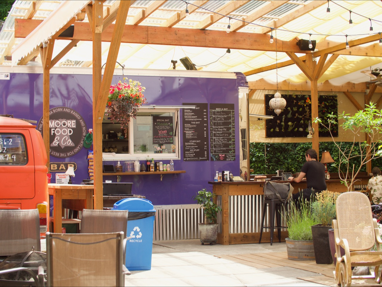 The purple Moore Food & Co cart is covered with an overhang, surrounded by a bar with an orange coffee van set up next door.