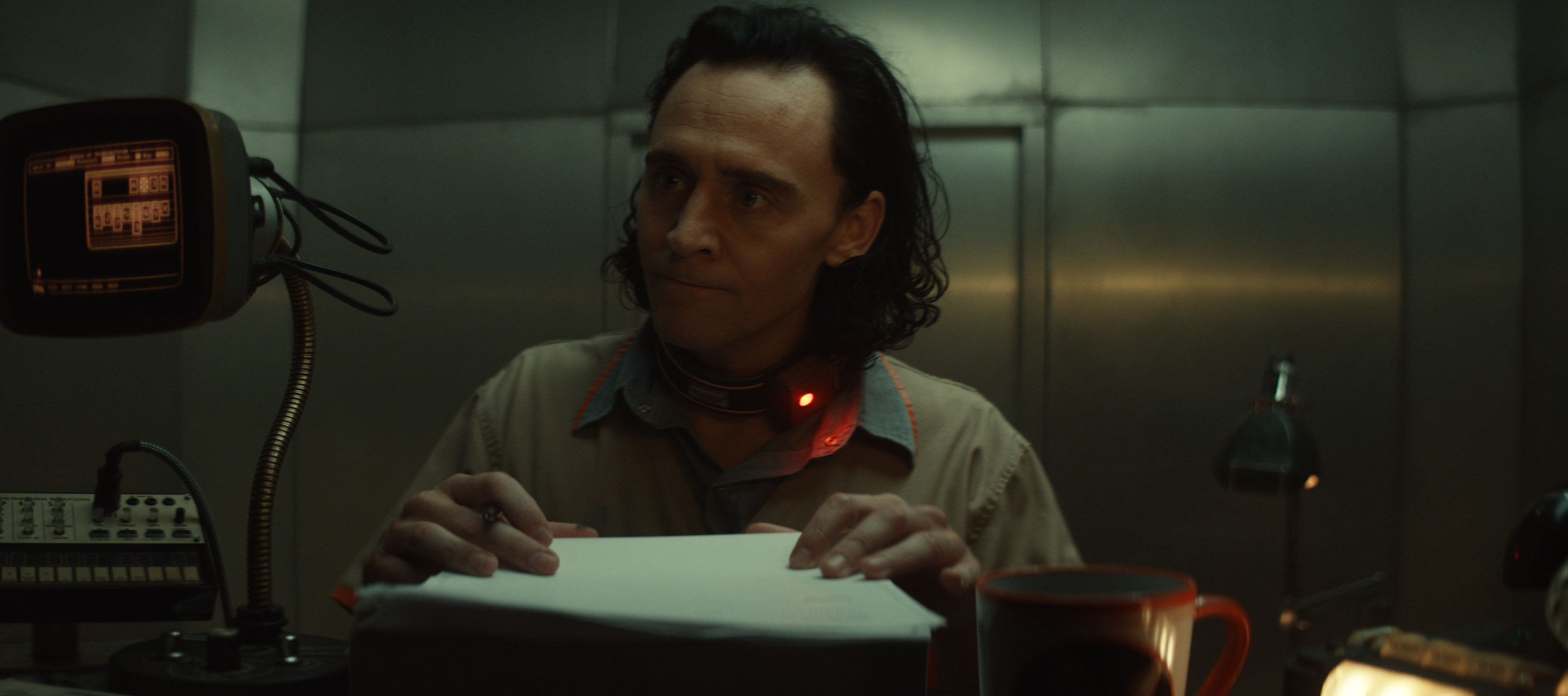 Loki furiously signs paperwork in the first episode of Loki