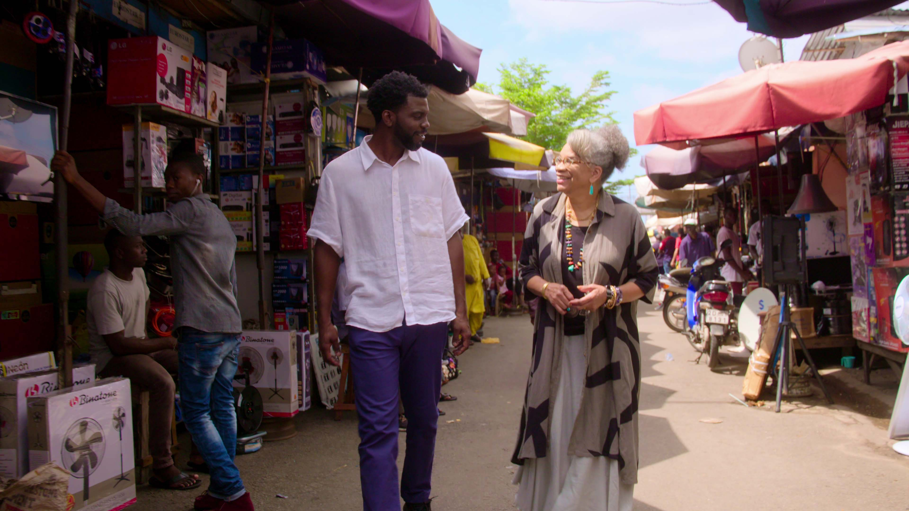 A man and woman walk in an outdoor market