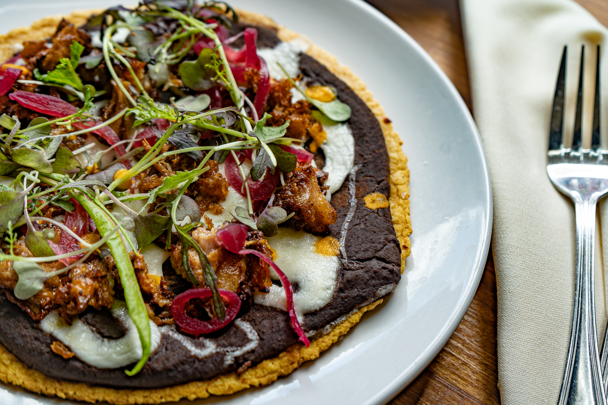 A flat tortilla topped with slow cooked pork, black beans, queso Oaxaca, annatto, citrus, pickled onions