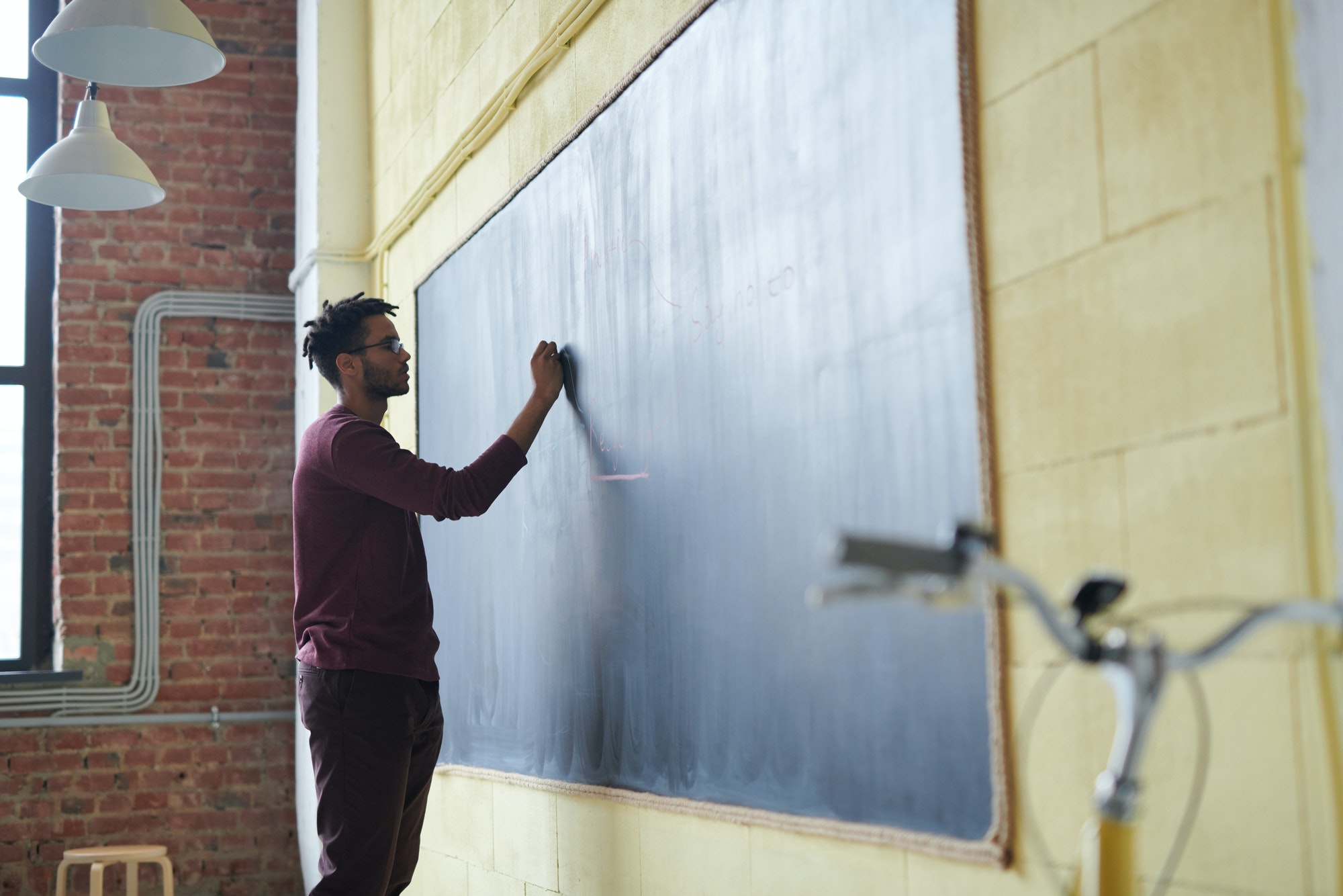A teacher writes on a blackboard
