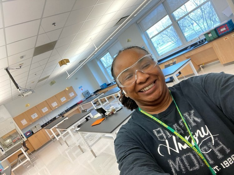 """A woman wearing safety goggles, a school lanyard and a shirt that says """"Black History Month"""" takes a selfie in her chemistry classroom."""