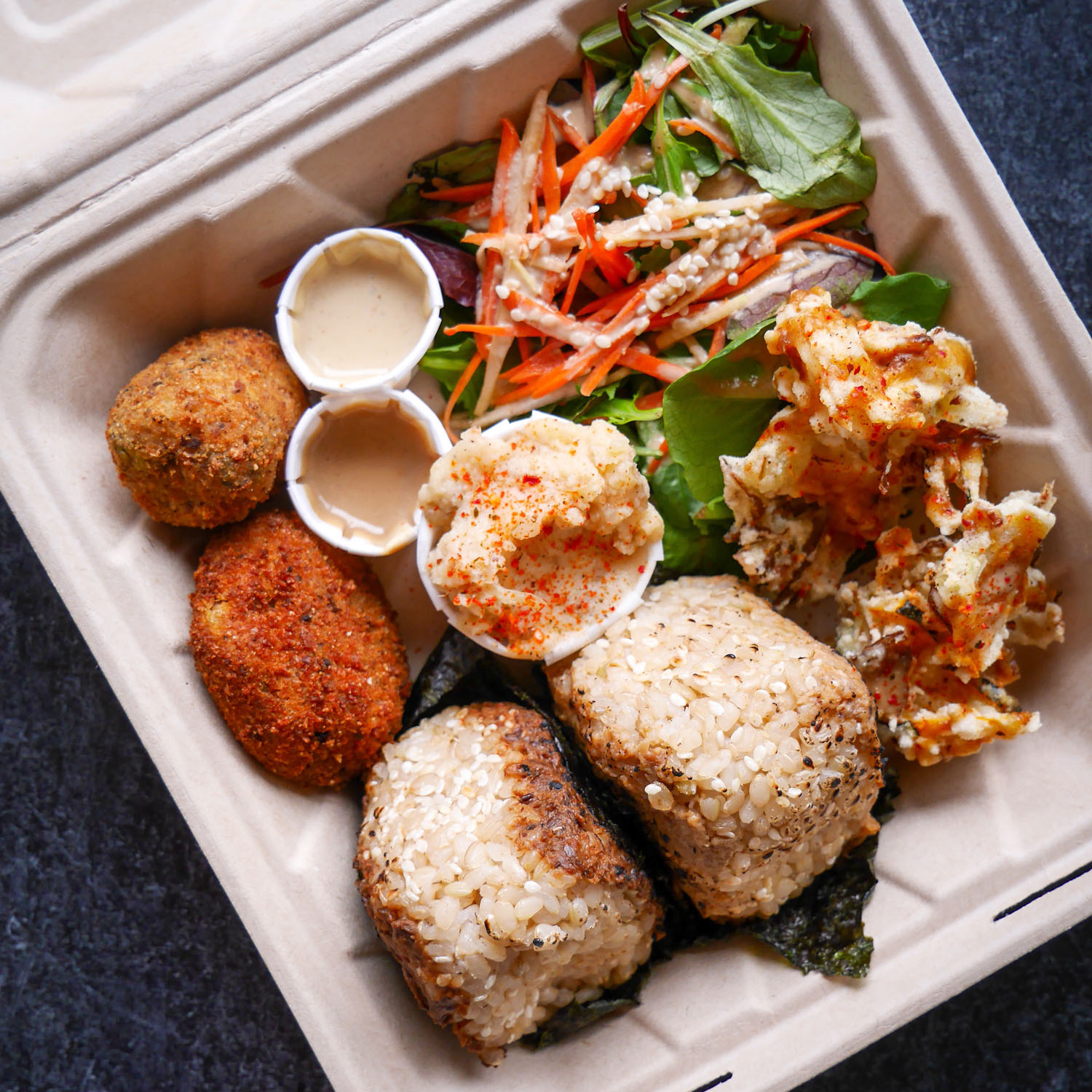 A photo of a takeout container with vegan onigiri, curried korokke, kakiage, giant tater tots, and salad from Obon Shokudo