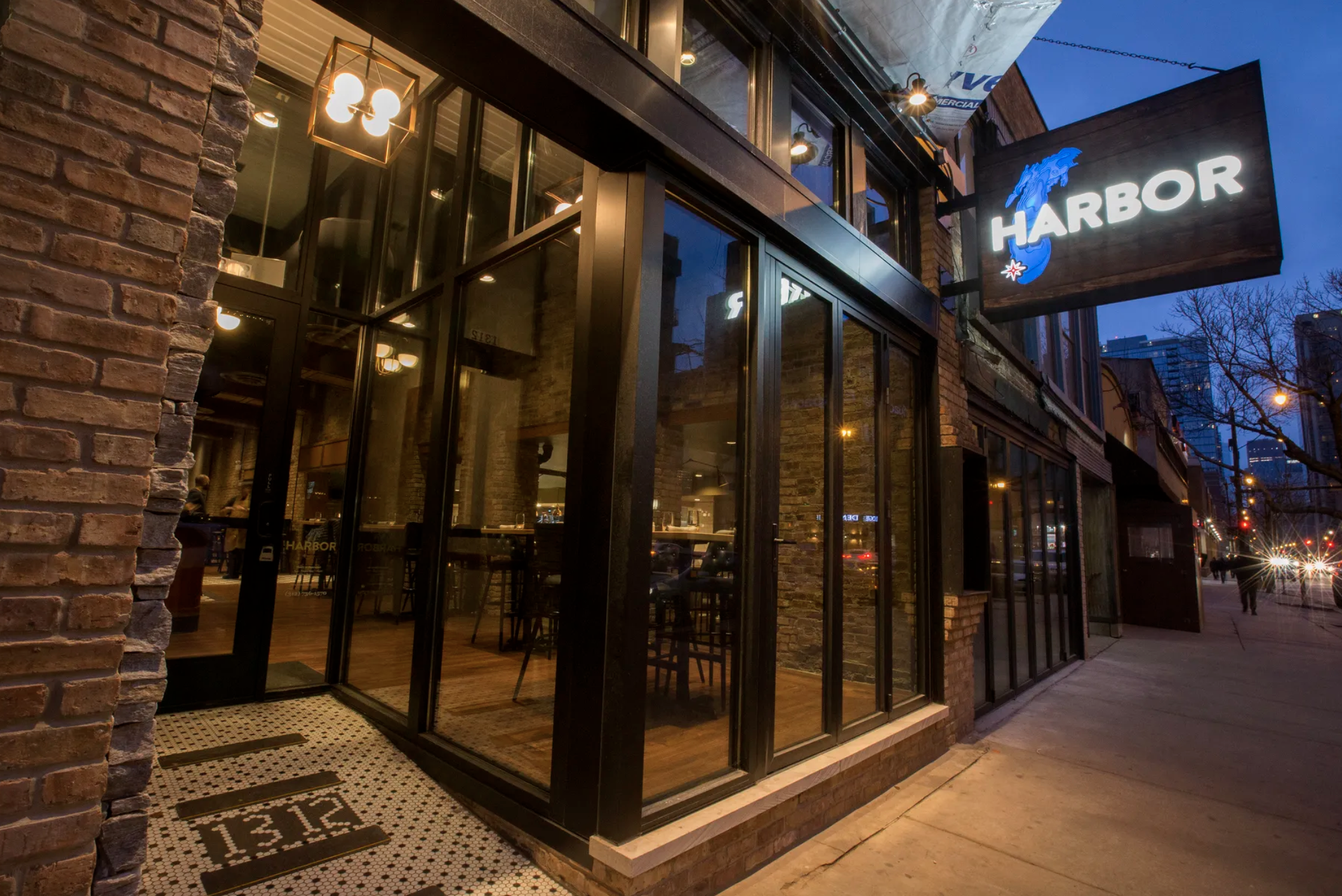 """A restaurant exterior with a sign that reads """"Harbor"""" over an outline of the Great Lakes"""