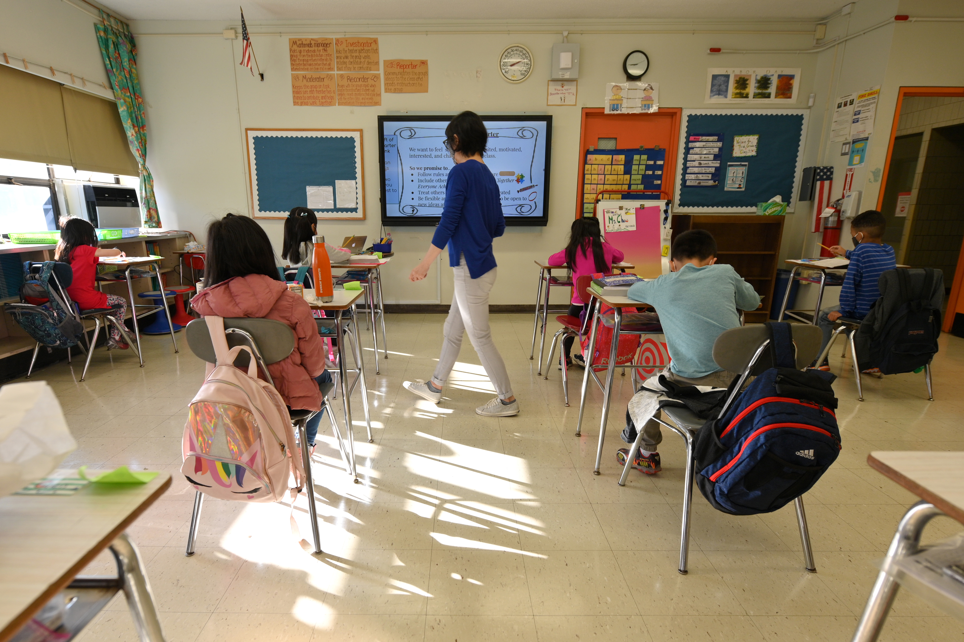 Students sit at their desks in a classroom during in-person instruction as their teacher walks through the room. There is a ray of light reflecting off of the floor of the classroom in between two rows of desks.