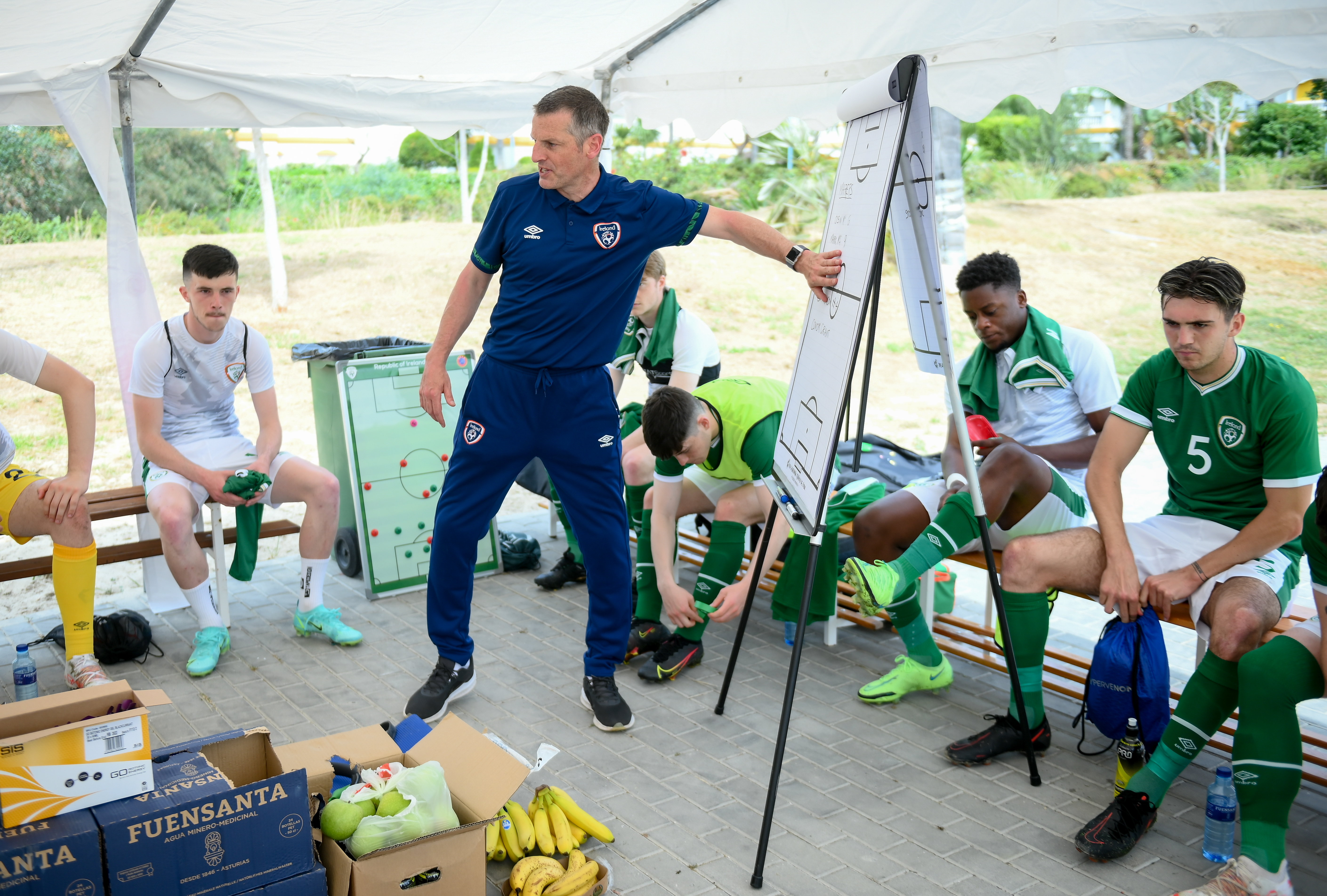 Manager outlines tactics to his players before an international match