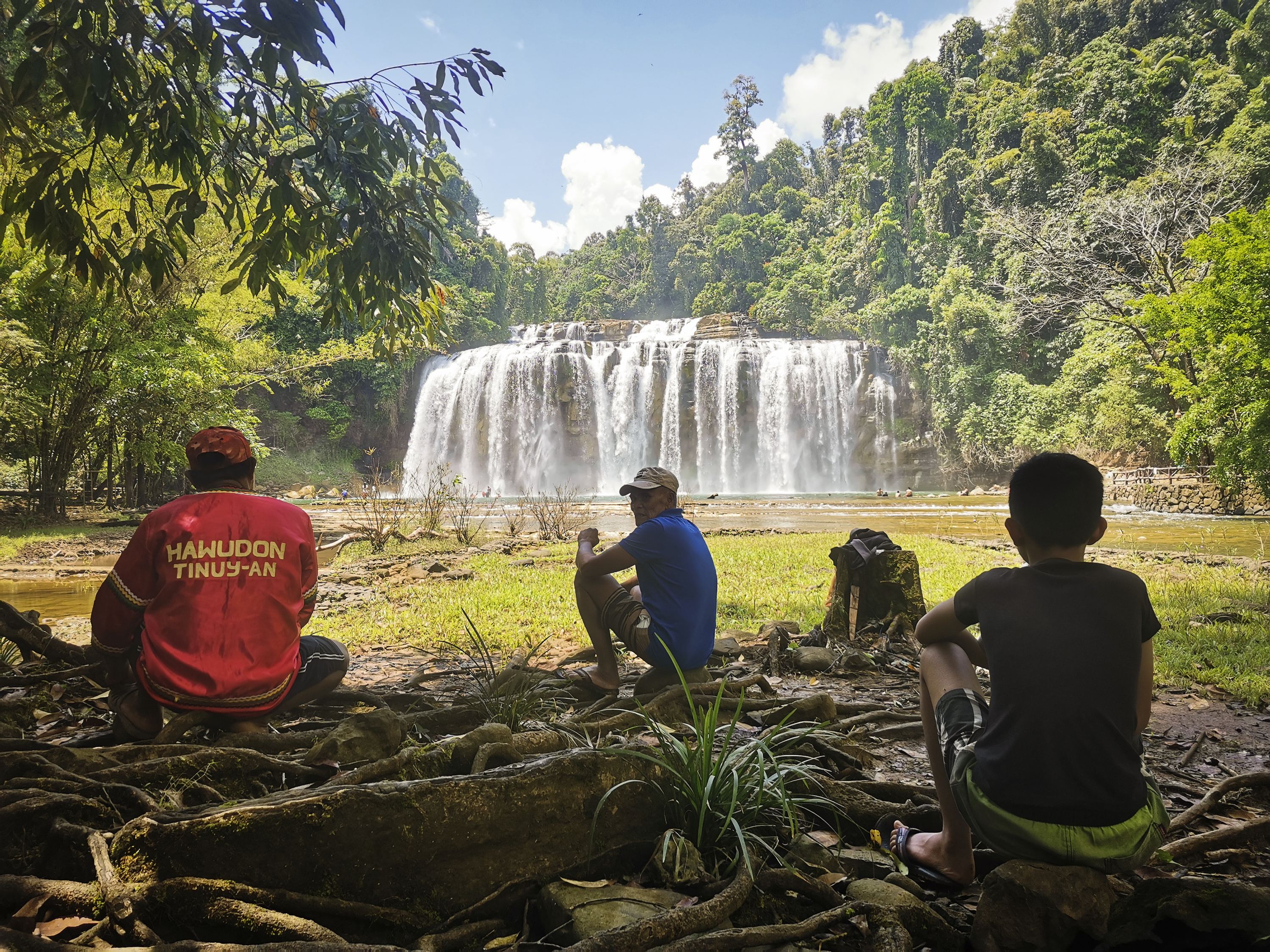 People sit across from a waterfall in a clearing in a lush forest.