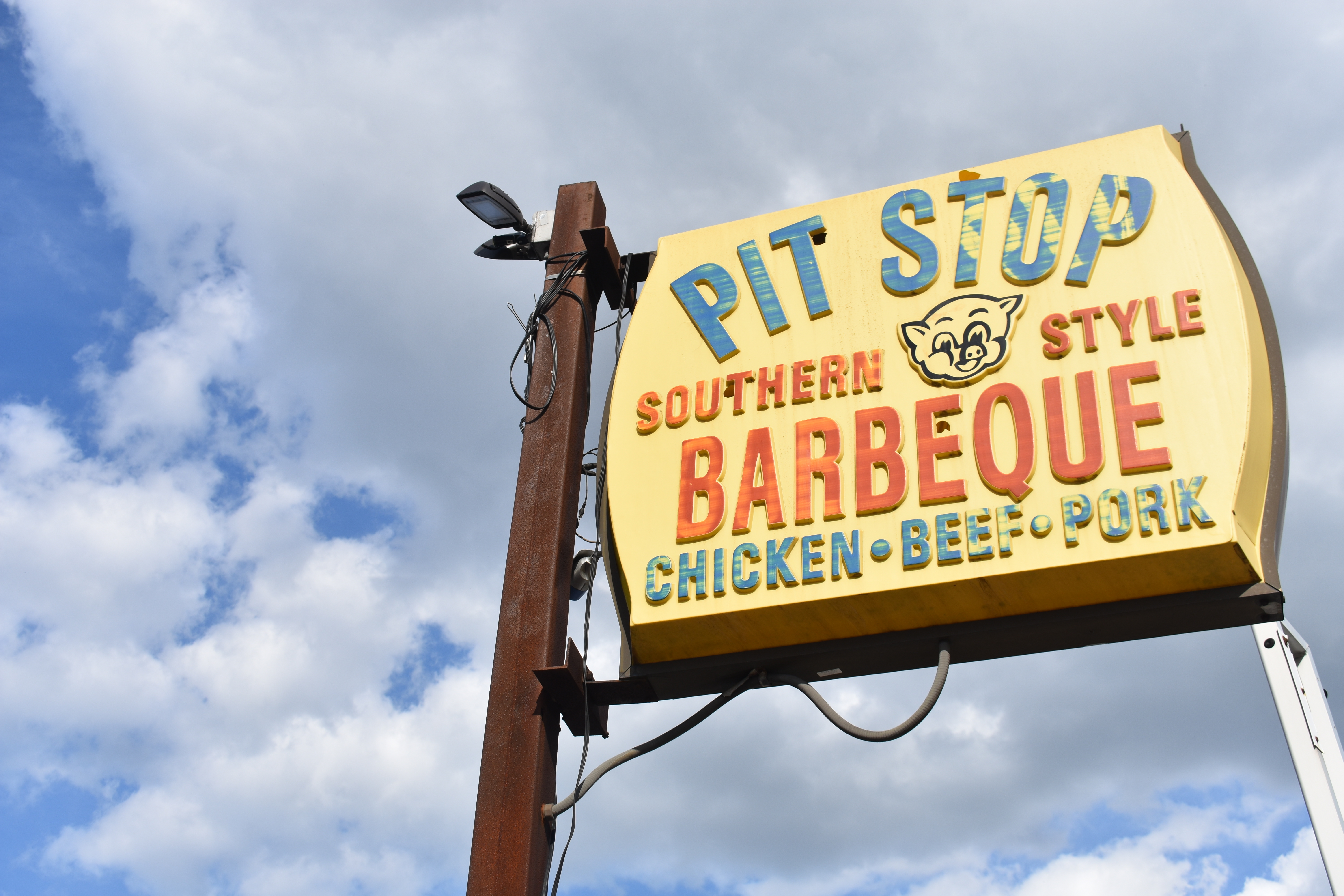 A faded restaurant sign is visible against a blue sky full of puffy white clouds. The sign says Pit Stop Southern Style Barbeque Chicken Beef Pork, and there's a cartoon image of a pig's face