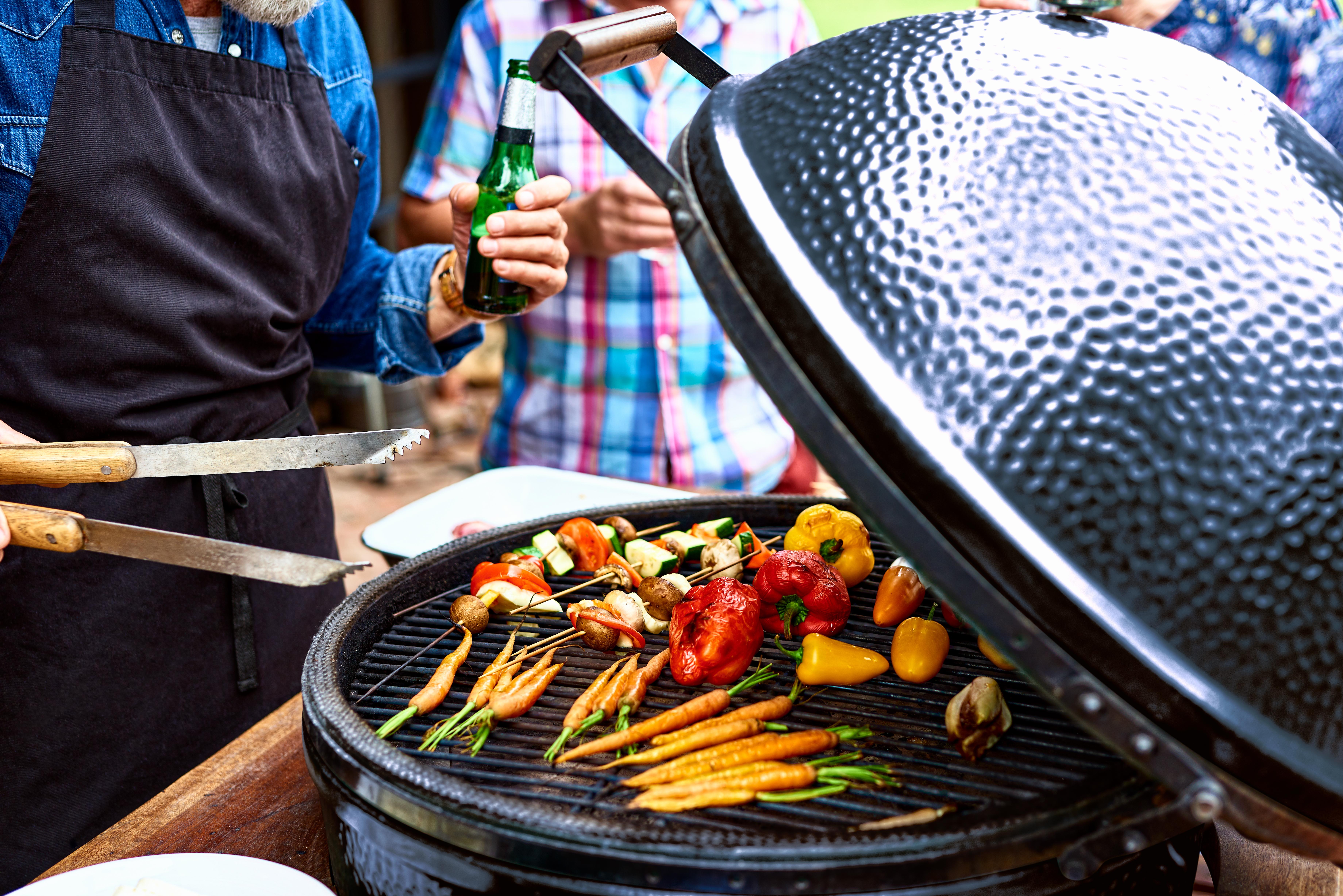 在水壶式木炭烤架上烤一组蔬菜;两个人站在它旁边,一个拿着一对钳子。