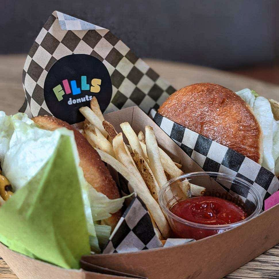 """Two burgers sit in black-and-white-checkered paper with medium-cut fries and a plastic cup of ketchup. The sticker on the paper reads """"Fills Donuts."""""""