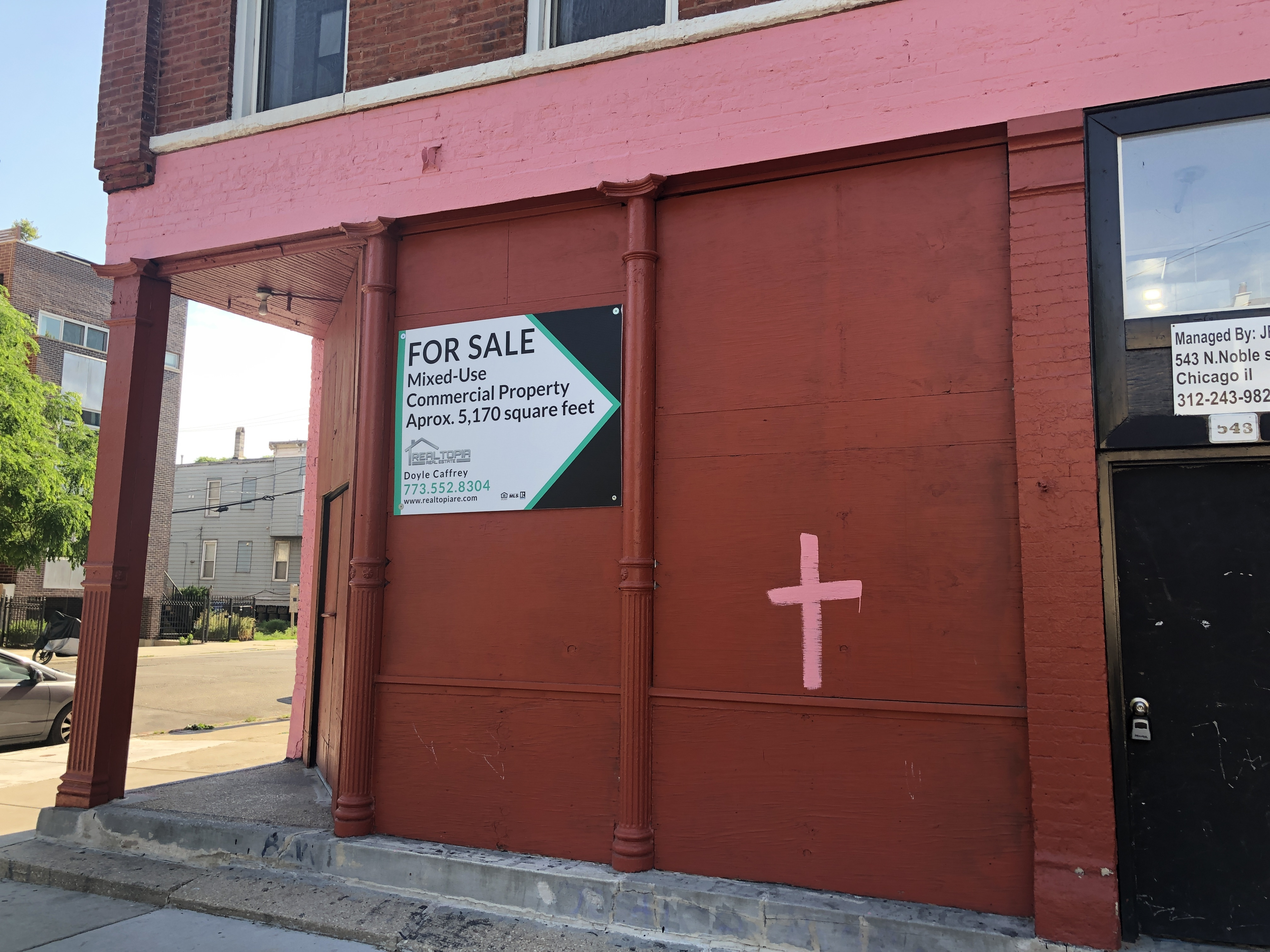 A red painted building with a pink cross.
