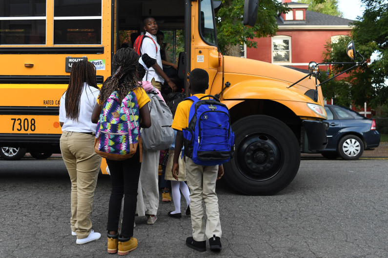 A group of students with their backs to the camera board a yellow school bus.
