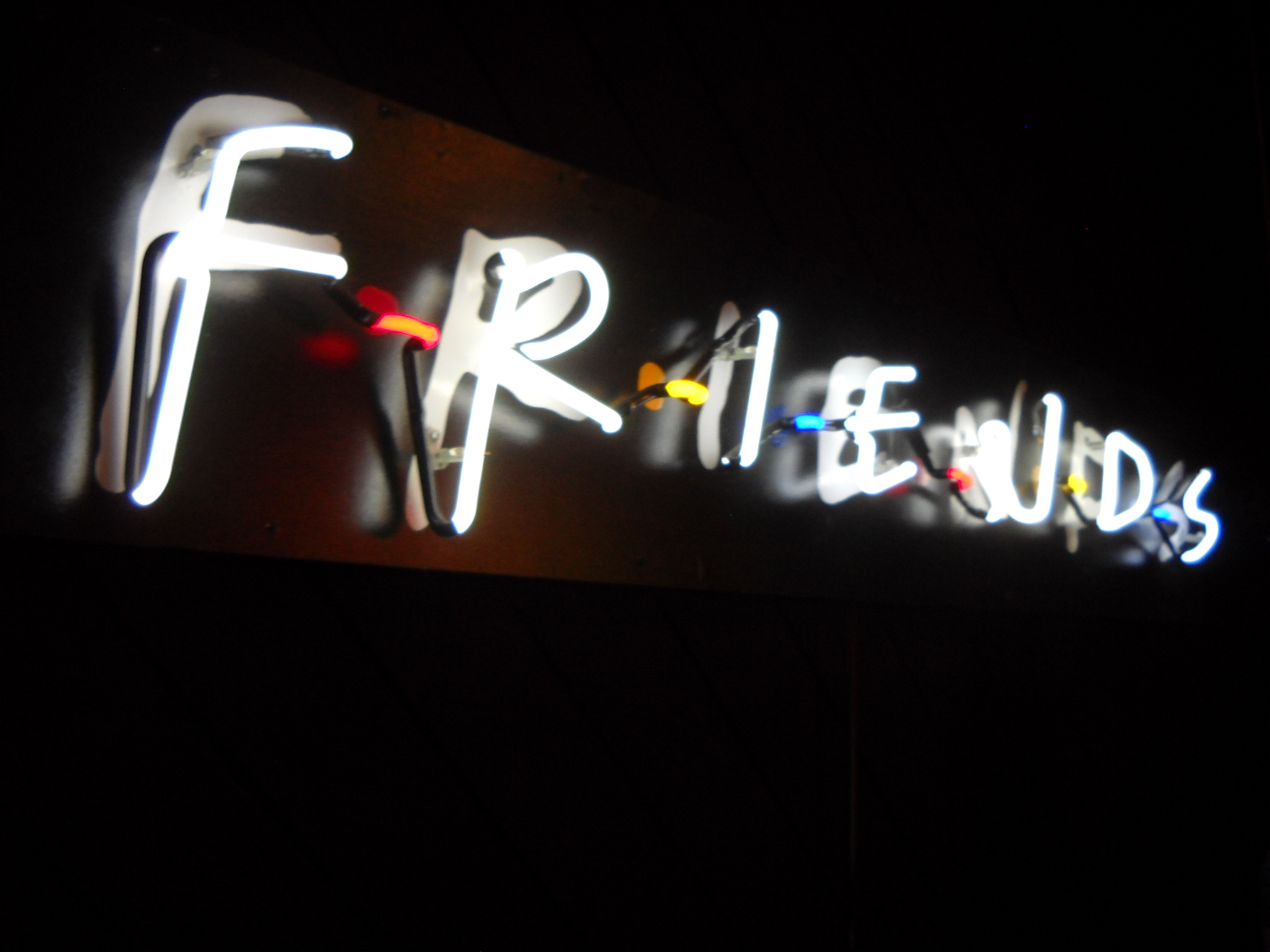 """A neon sign glows in the night, showing the """"Friends"""" sitcom logo."""