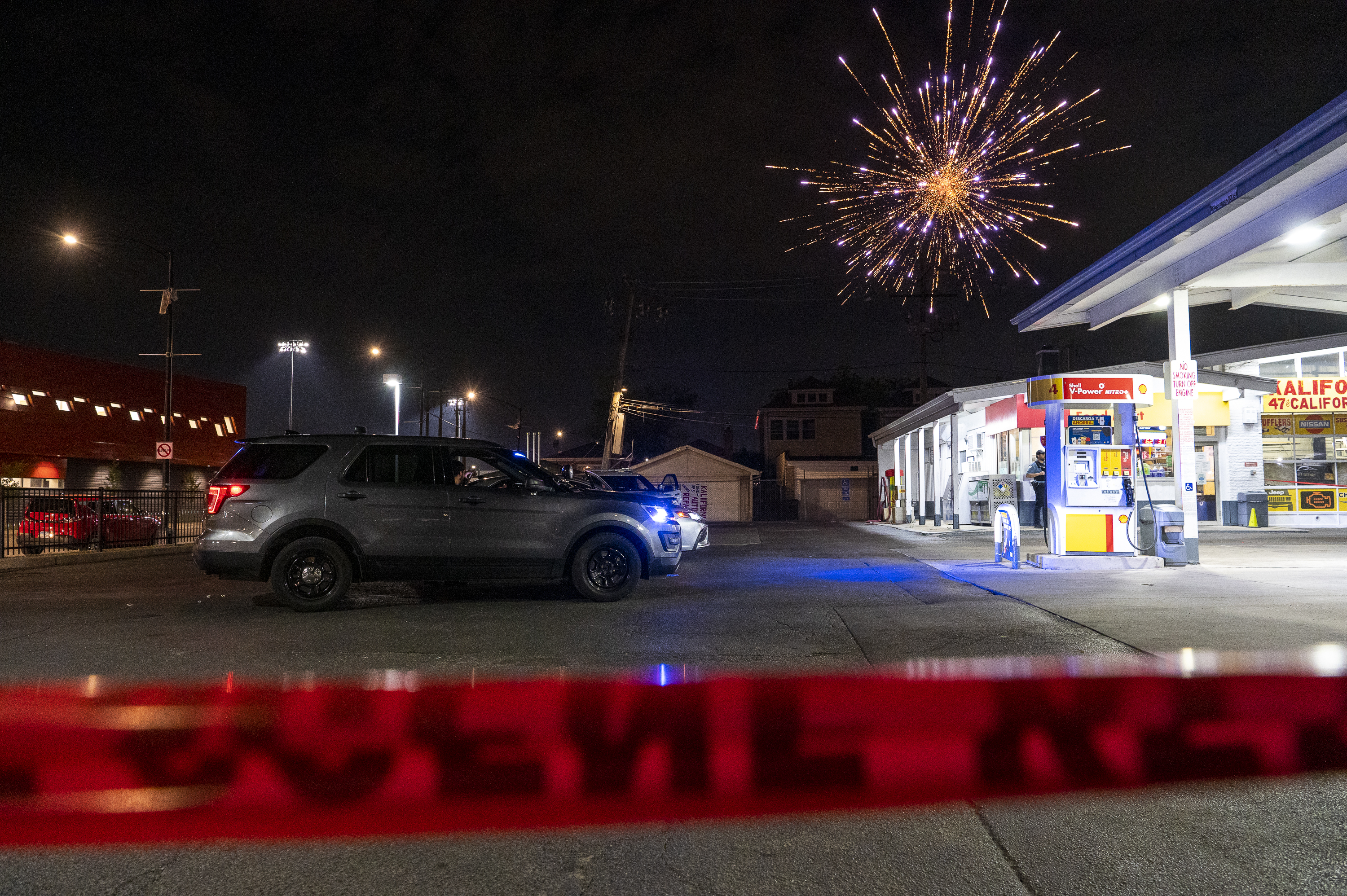 A fireworks explodes in the air as Chicago police work the scene were a 20-year-old woman was shot in 4700 block of South California Ave, in the Brighton Park neighborhood, Friday, June 11, 2021. The shooting initially took place near the 4700 block of South Rockwell.