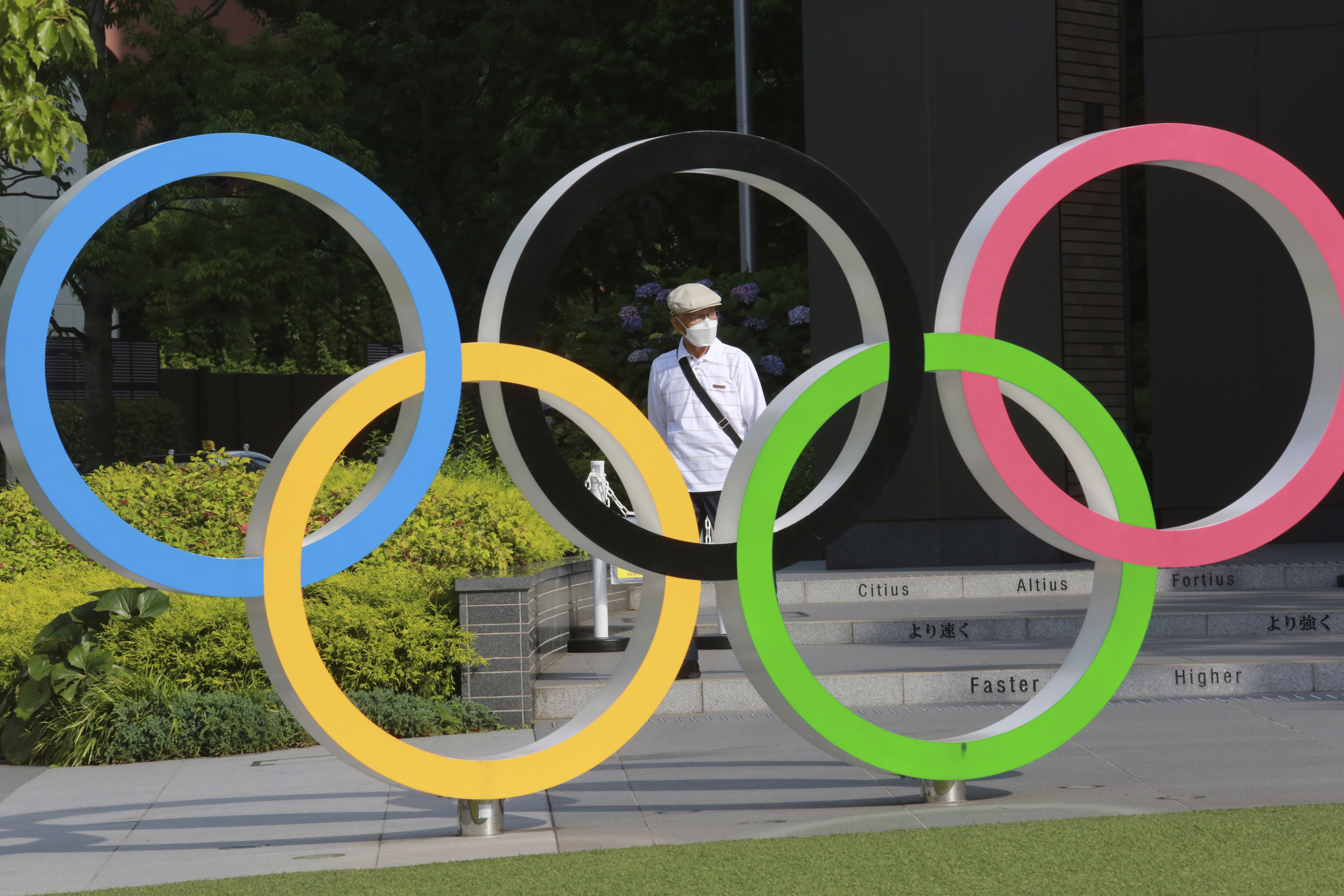 A man walks past the Olympic rings in Tokyo in 2021.