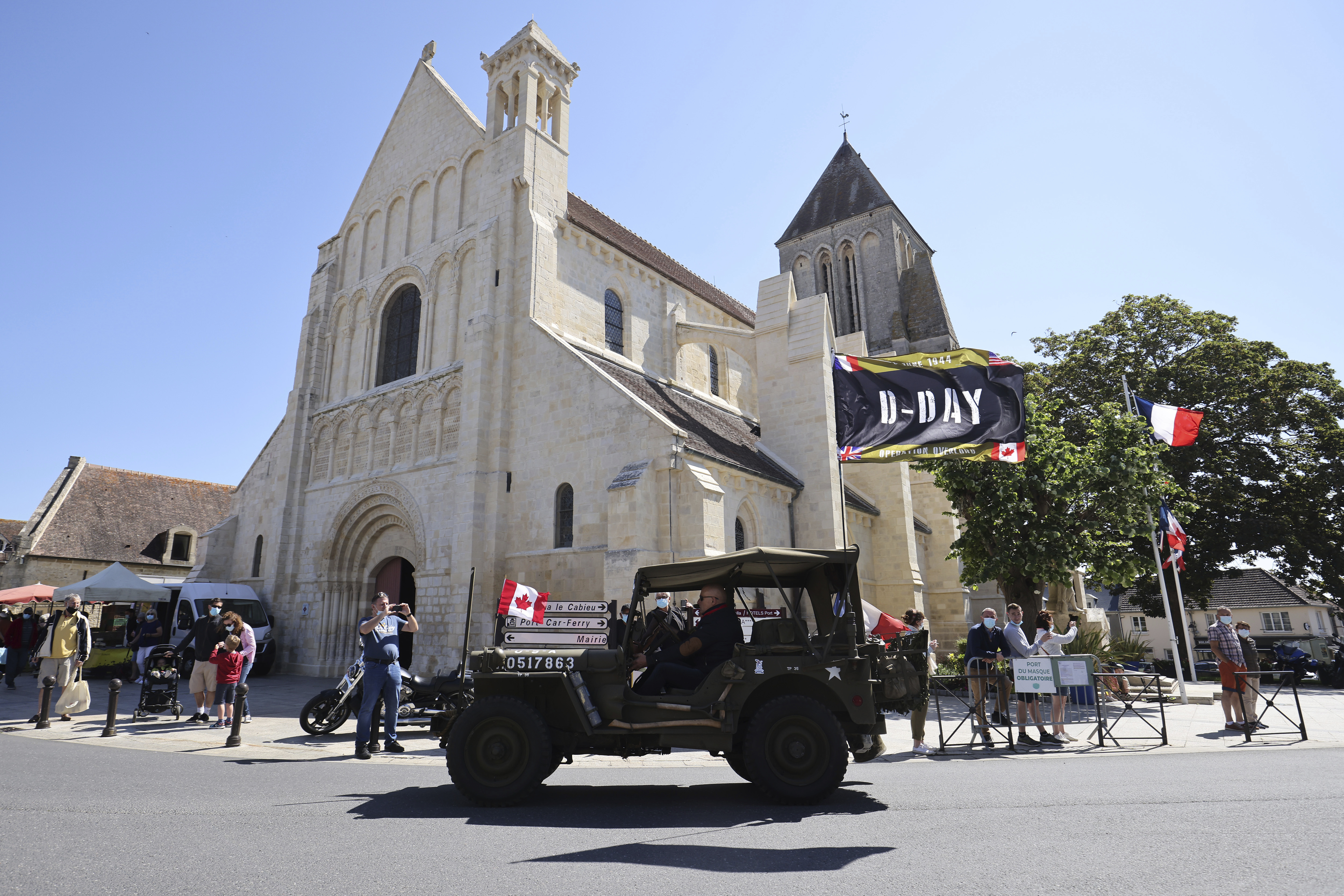 World War II history enthusiasts parade in WWII vehicles in Ouistreham, Normandy.