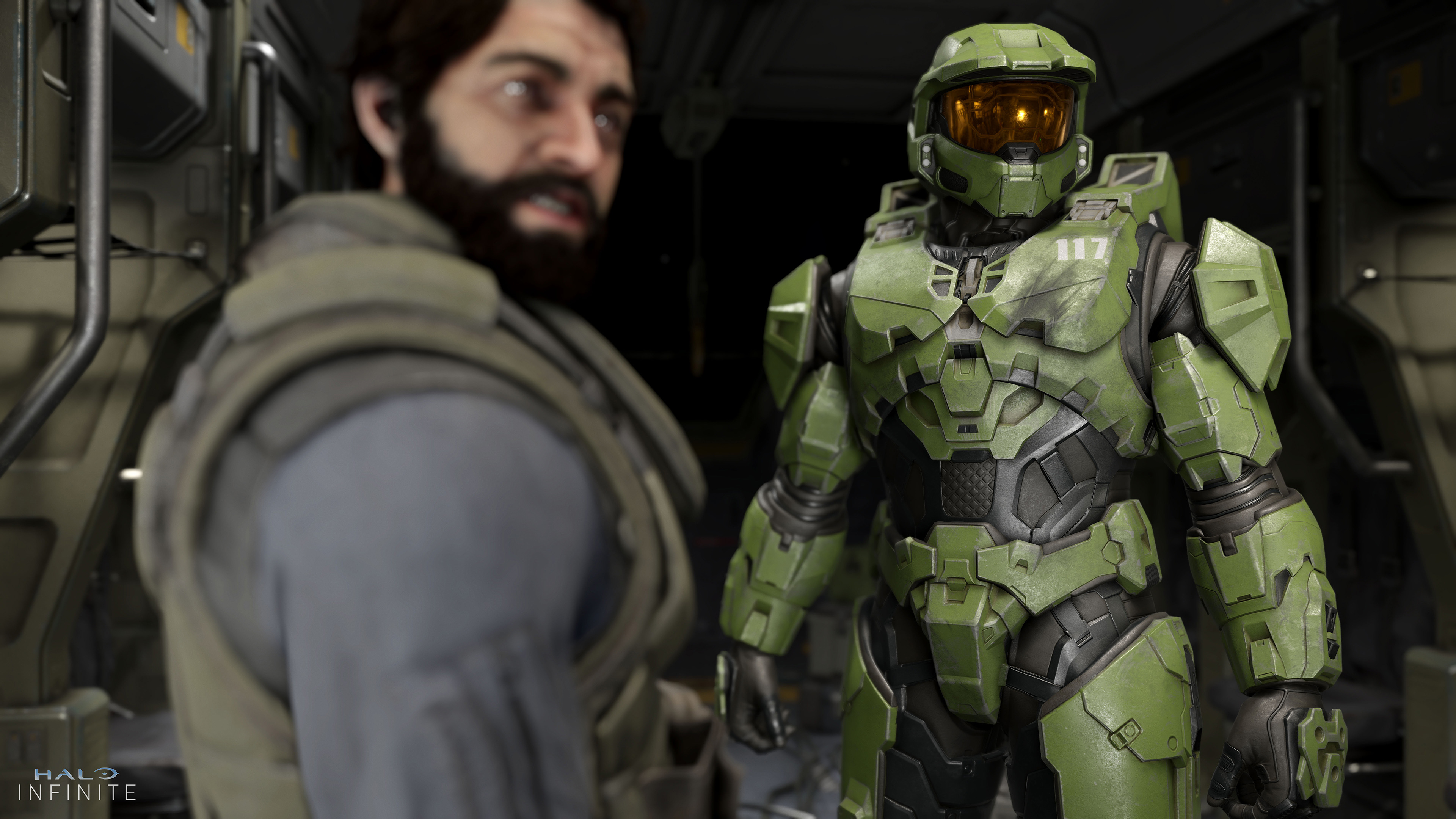 a dark-haired bearded man and Master Chief look to the right in Halo Infinite
