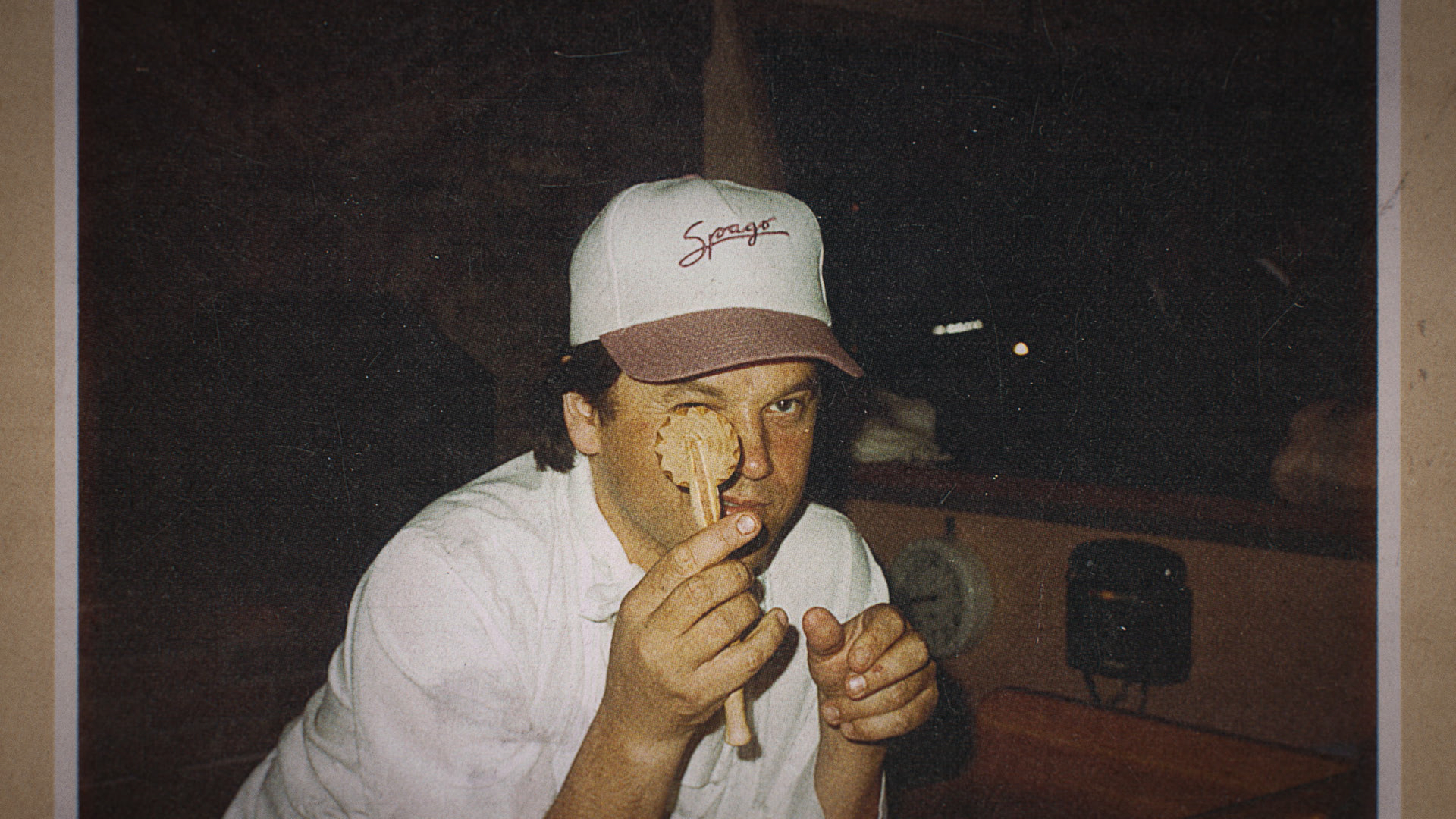 A young man, Wolfgang Puck, in a Spago baseball hat holding a ravioli cutter up to his eye
