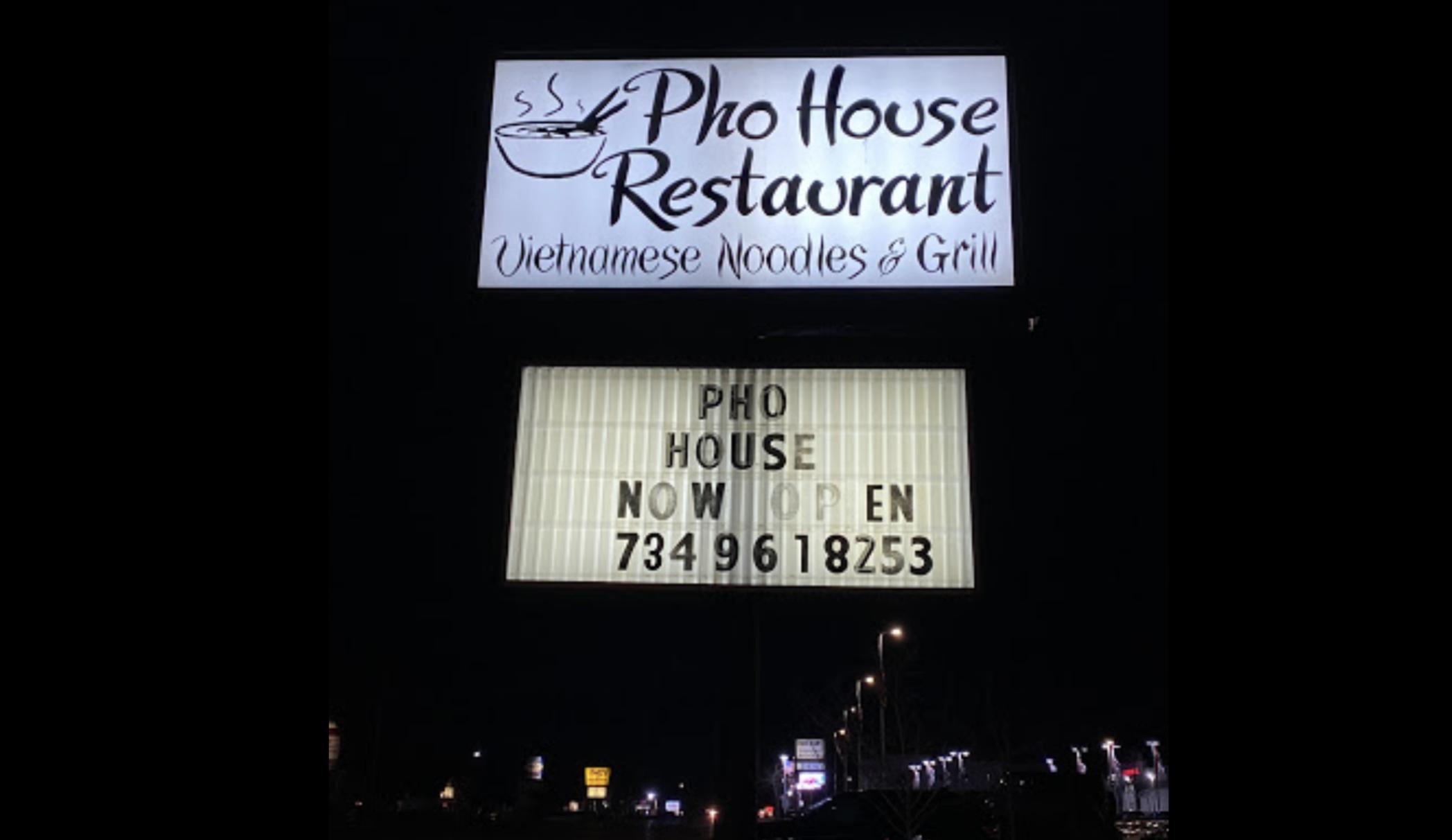 """晚上,马路上的phoo House餐厅的招牌上写着""""现在开门"""",并列出了一个电话号码。"""