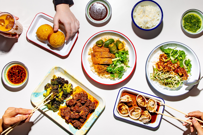 菠萝面包,云南胸部,四川花椰菜,馄饨,鸳鸯和其他菜肴在一张白色的桌子上拍摄开销