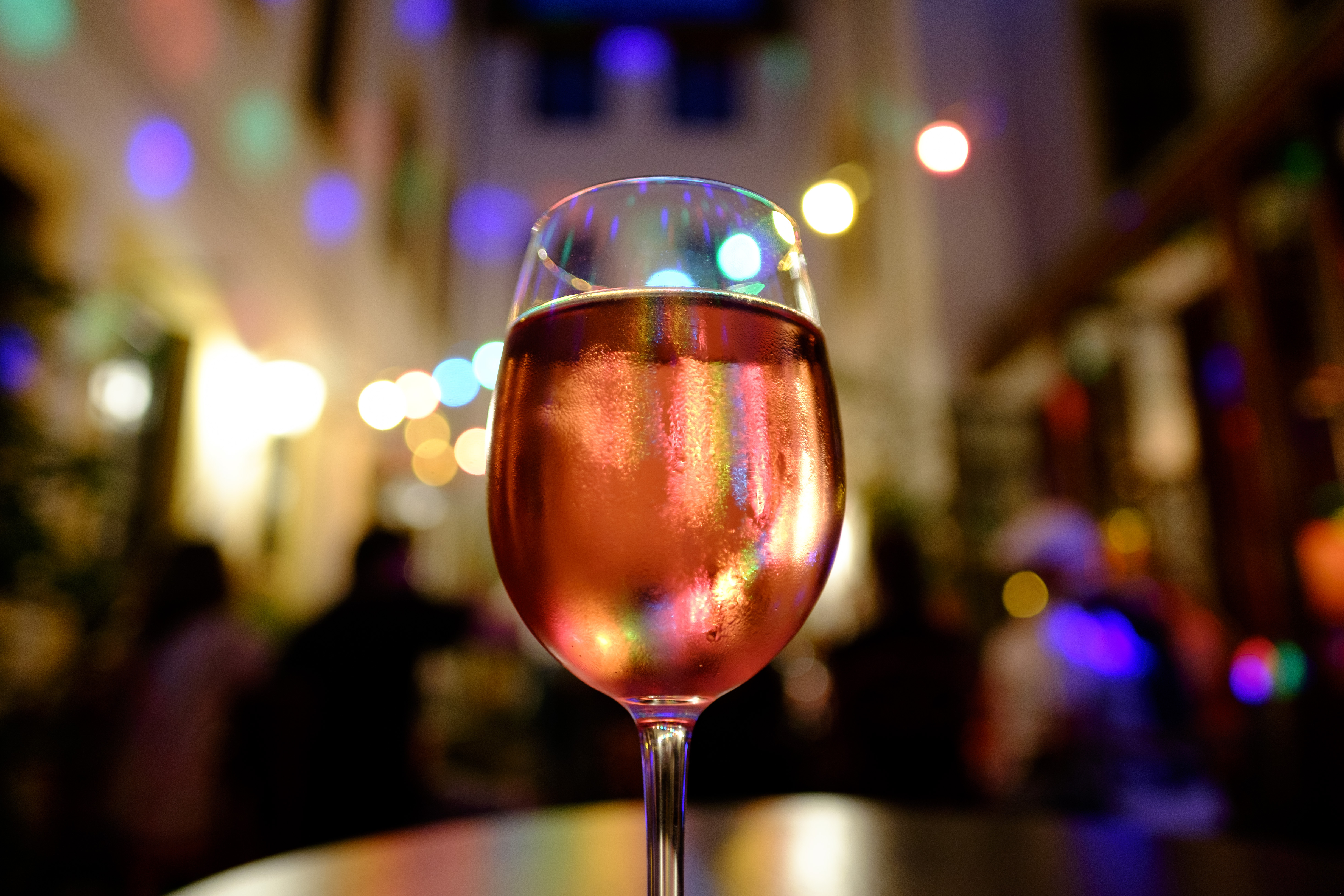 A close up on a large glass of pink wine with a twinkly night time backdrop