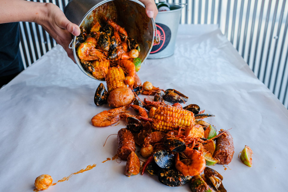 A bucket of sauced shrimp, mussels, crawfish, sausage and corn on the Crab N Spice menu headed to Chinatown.