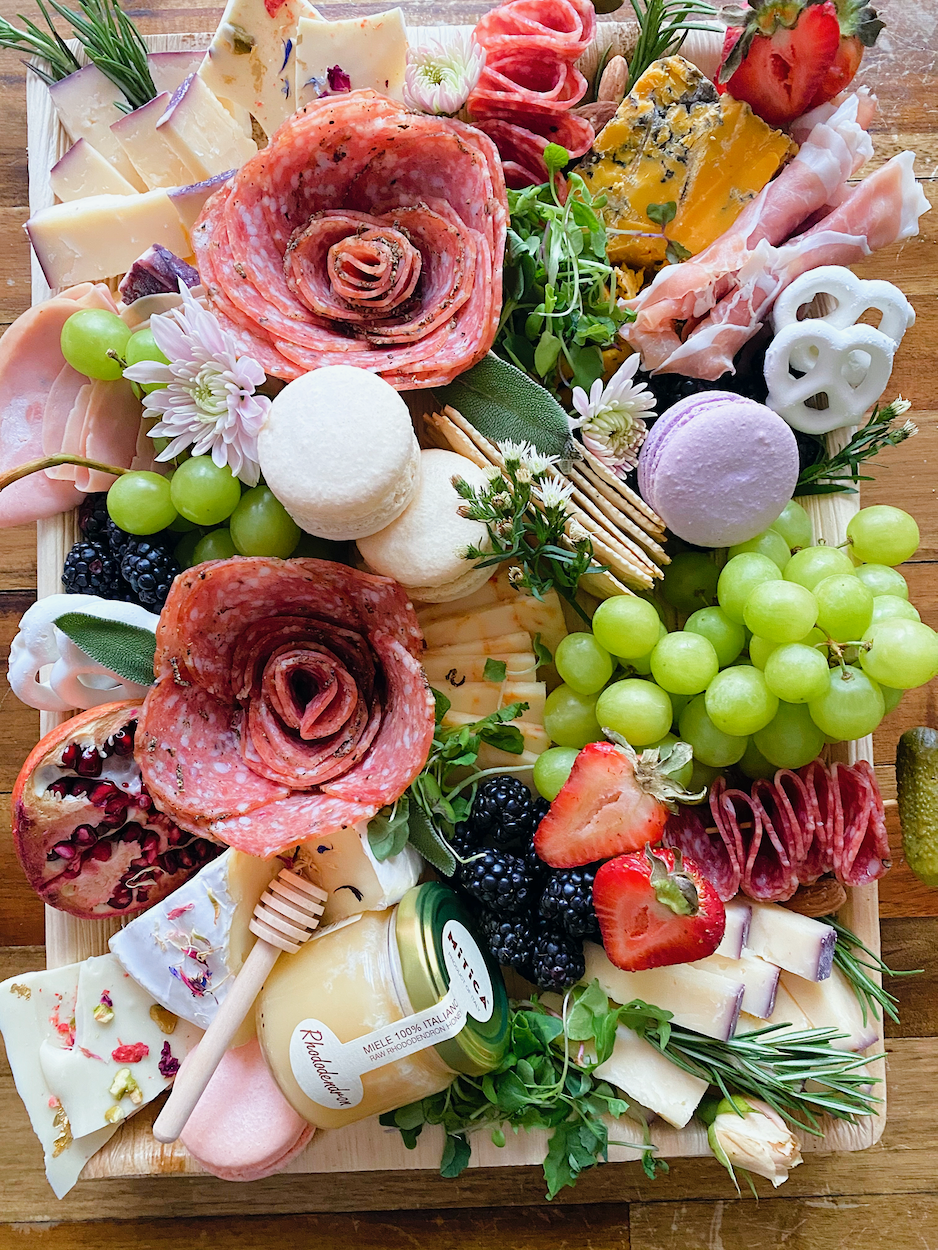 A platter of cheese, grapes, cured meats, crackers, strawberries, and a macaron