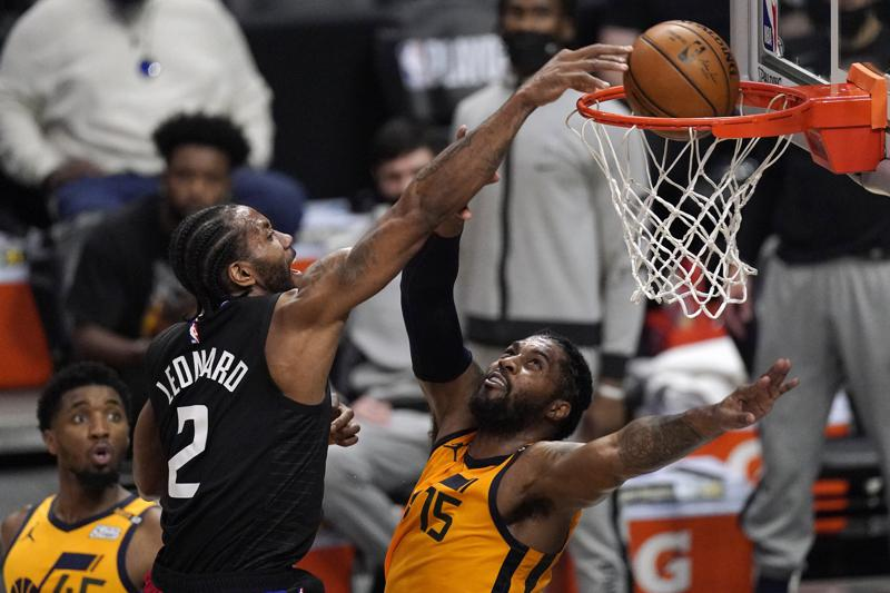 Los Angeles Clippers forward Kawhi Leonard, center, dunks over Utah Jazz center Derrick Favors, right, as guard Donovan Mitchell watches during the first half in Game 4 of a second-round NBA basketball playoff series in Los Angeles.
