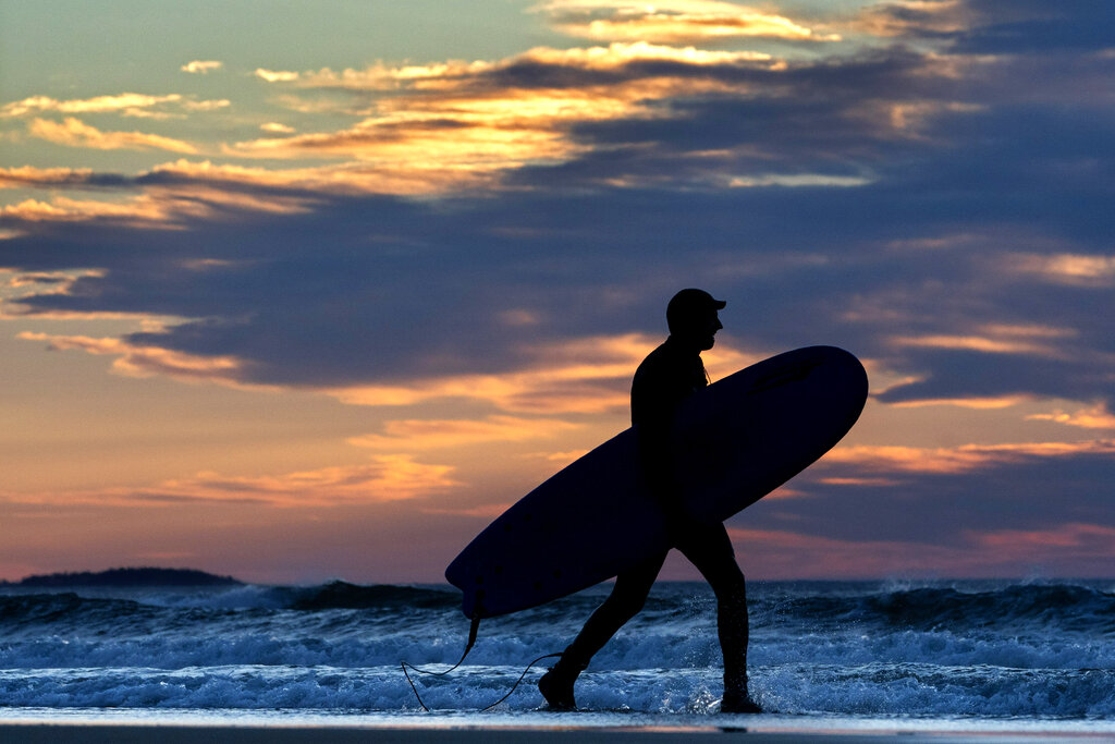 A surfer heads out to ride the waves at Old Orchard Beach, Maine.