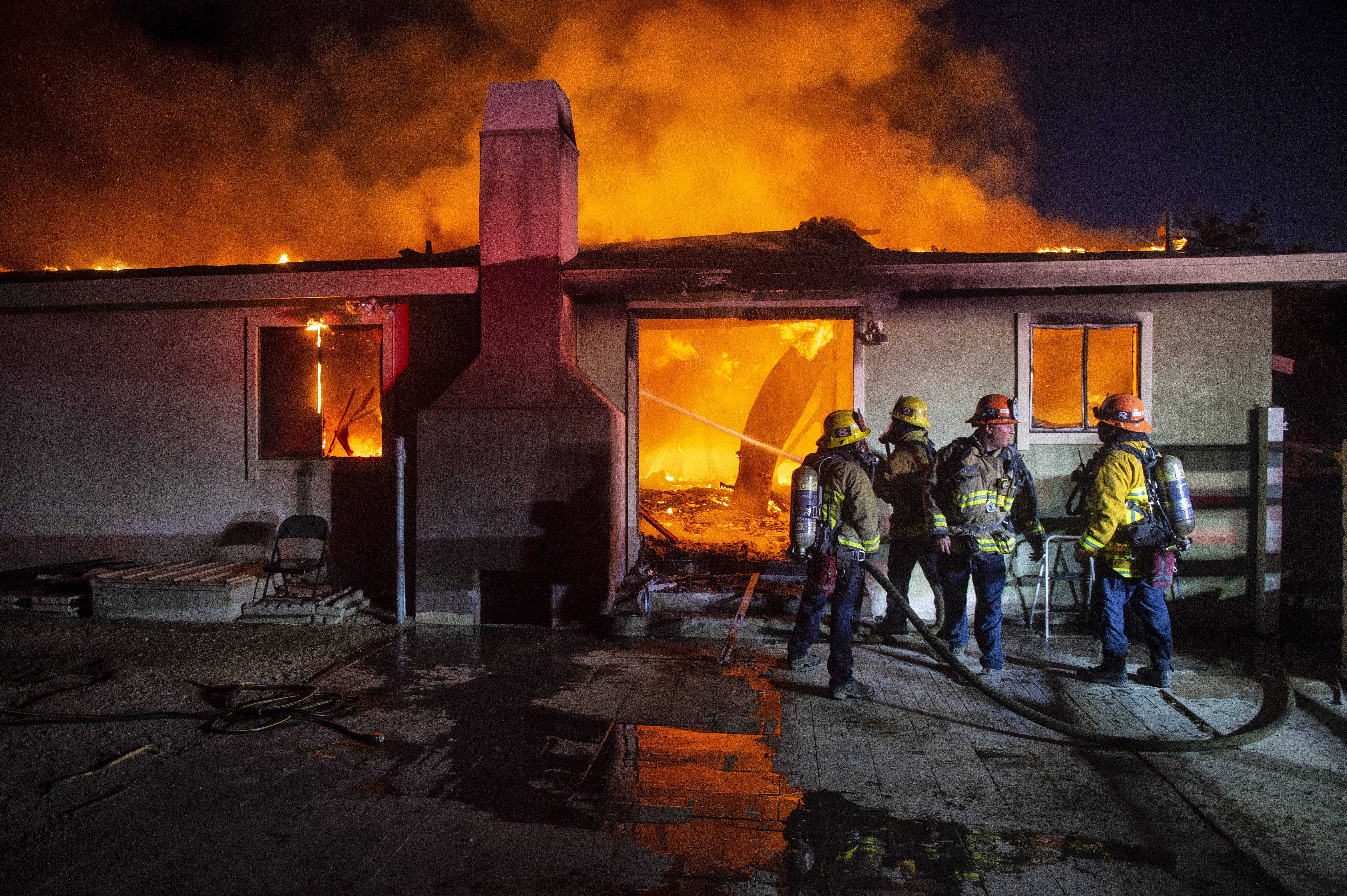 Firefighters outside a burning home.