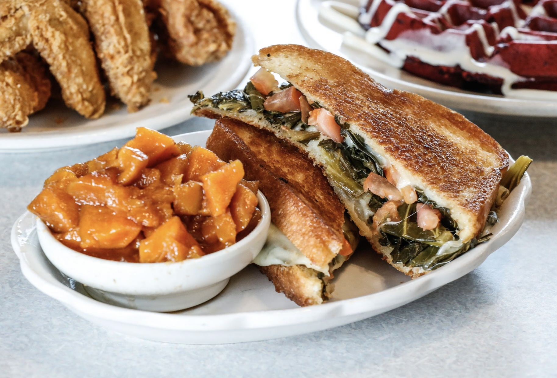 厚厚的烤奶酪,切成两半,堆在盘子里,旁边是一碗蜜饯甘薯。这种三明治里有羽衣甘蓝、番茄丁和奶酪