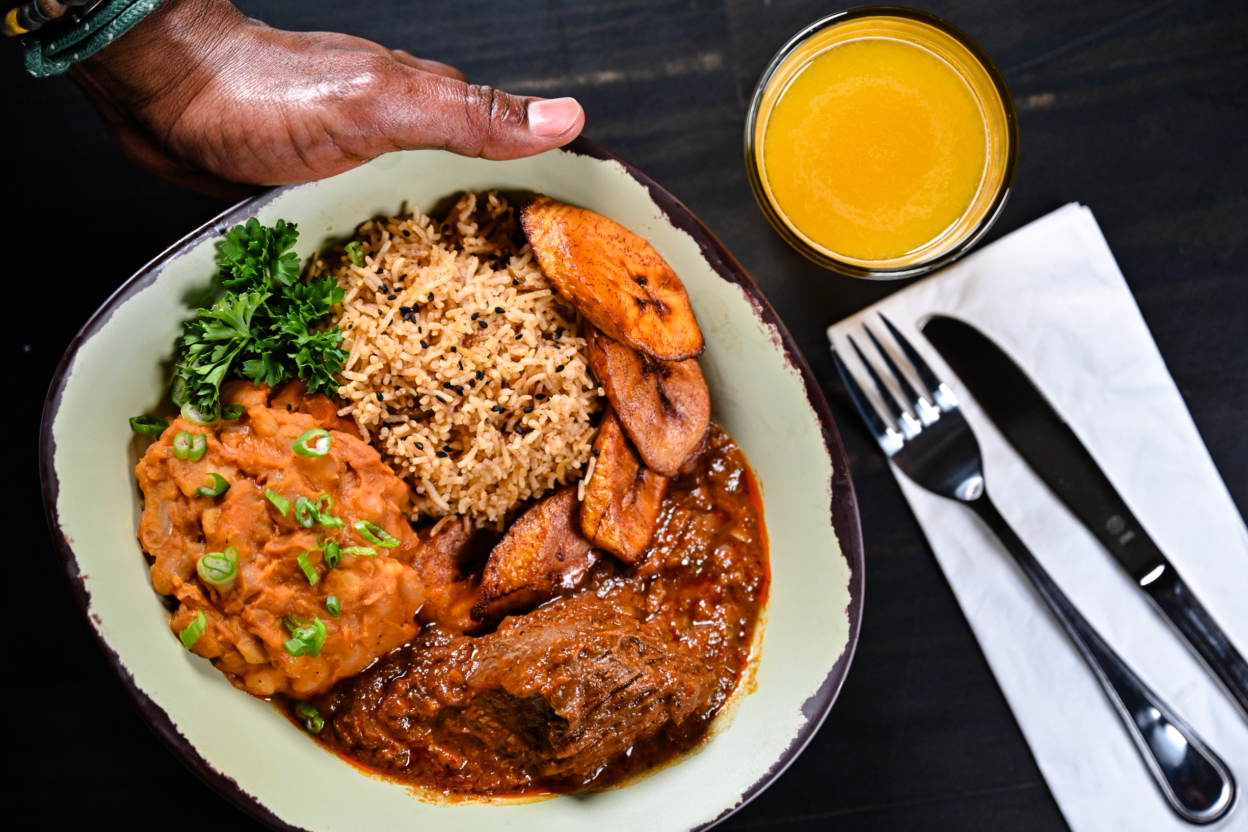 A hand holds a bowl filled with Nyumbani filled with several stews and slice plantains with a glass of yellow fruit juice next to it.