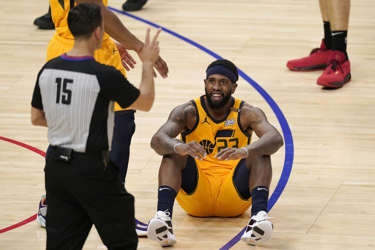 Utah Jazz forward Royce O'Neale, right, sits on the floor after committing a foul.