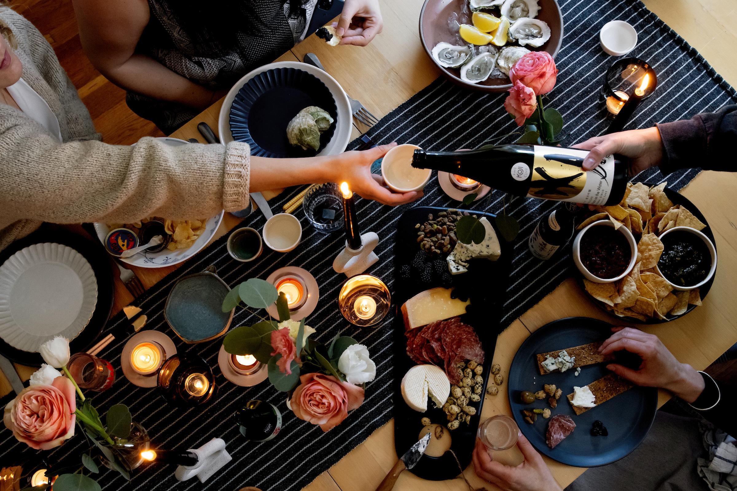 头顶上,一群人把清酒倒在桌子上。桌子上还有牡蛎。
