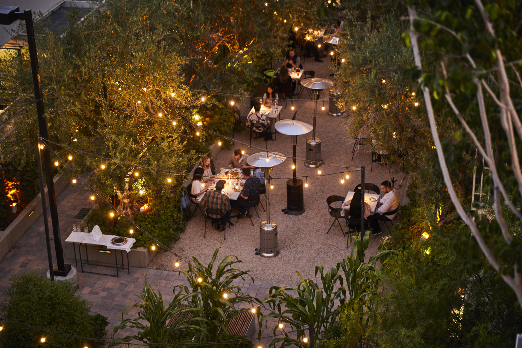 Outdoor dining at dusk with twinkle lights.